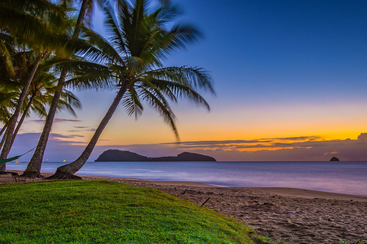beauty in nature, nature, scenics, sea, sunset, water, tranquil scene, tranquility, sky, outdoors, beach, palm tree, no people, landscape, horizon over water, tree, growth, grass, day