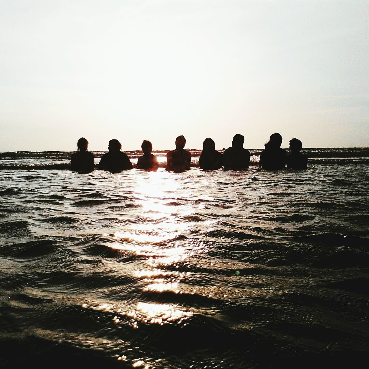 water, large group of people, leisure activity, sea, silhouette, vacations, lifestyles, sunlight, real people, men, sky, outdoors, sunset, togetherness, horizon over water, nature, swimming pool, women, scenics, day, clear sky, friendship, beauty in nature, people