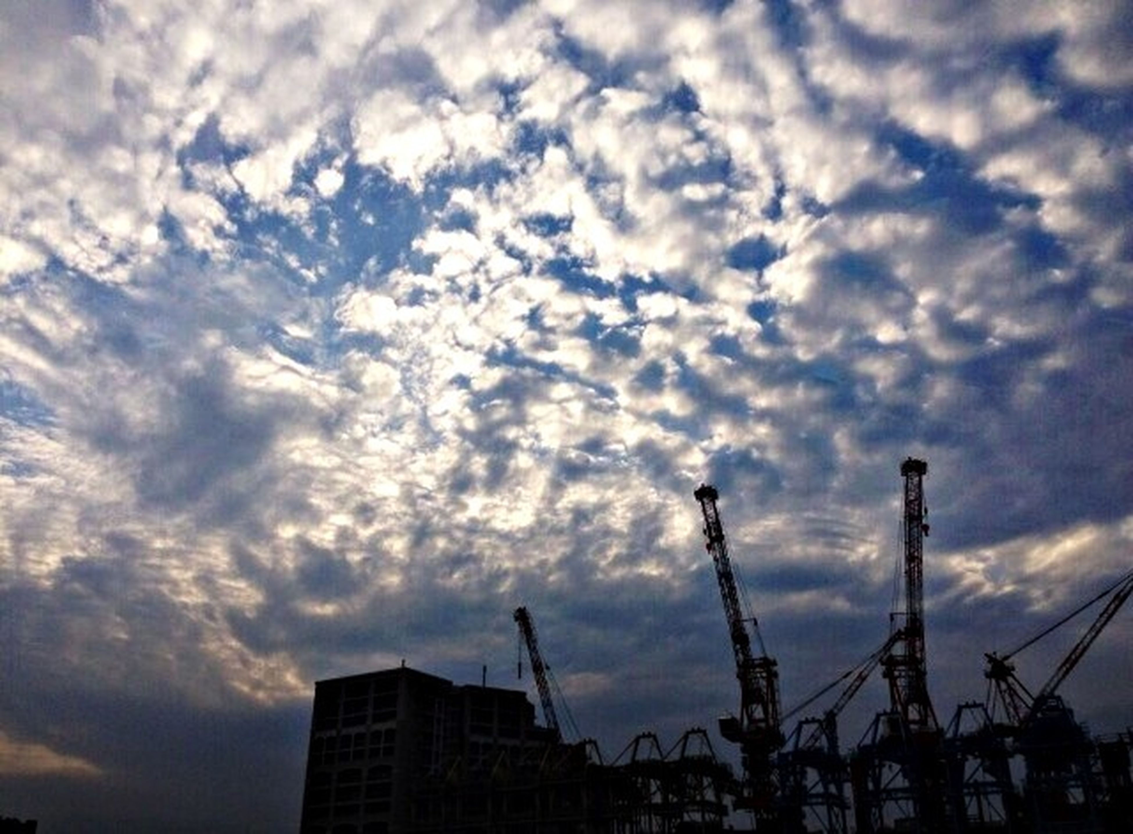 sky, architecture, built structure, building exterior, cloud - sky, low angle view, cloudy, city, silhouette, cloud, sunset, weather, crane - construction machinery, tall - high, building, development, dusk, skyscraper, overcast, outdoors