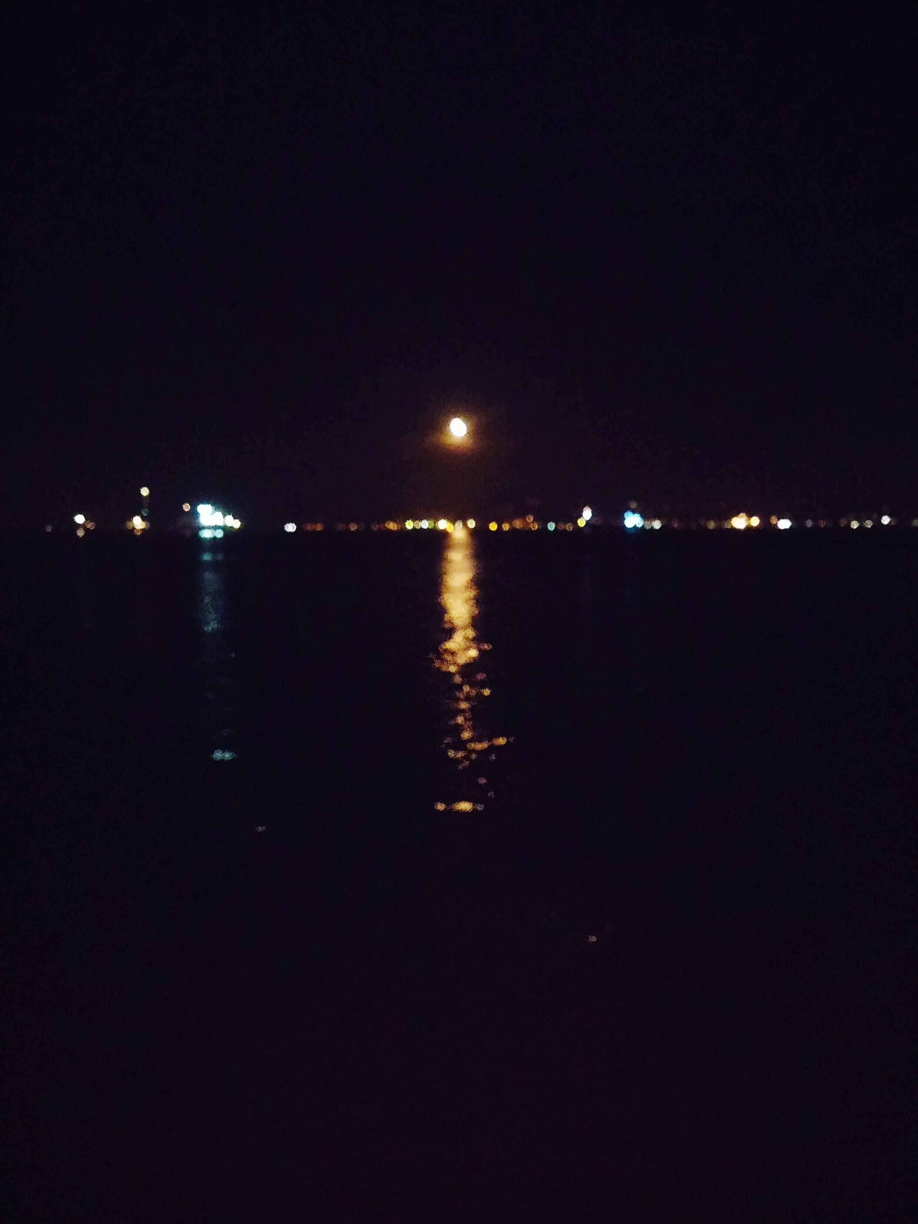 water, night, illuminated, reflection, clear sky, waterfront, copy space, sea, tranquil scene, tranquility, dark, scenics, river, lighting equipment, beauty in nature, nature, no people, built structure, rippled, outdoors