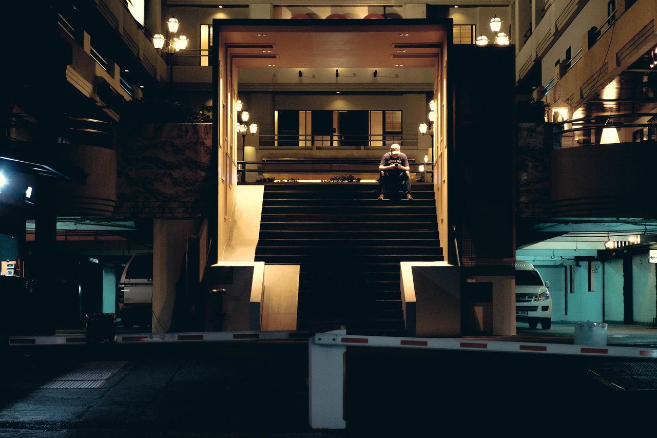 Distracted. Street Photography Contrast Shadow Man Thai Thailand Moody The Street Photographer - 2016 EyeEm Awards Bangkok Phone Distracted Sitting Sitting Man Night Nightlife Alone Alone In The Ci Alone At Night