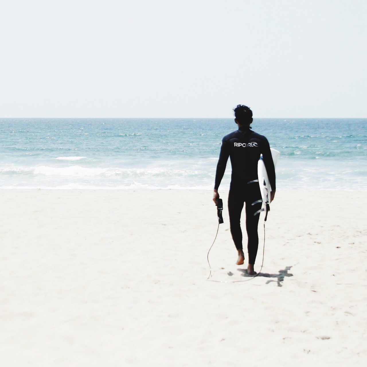 Full Length Rear View Of Man With Surfboard Walking At Beach