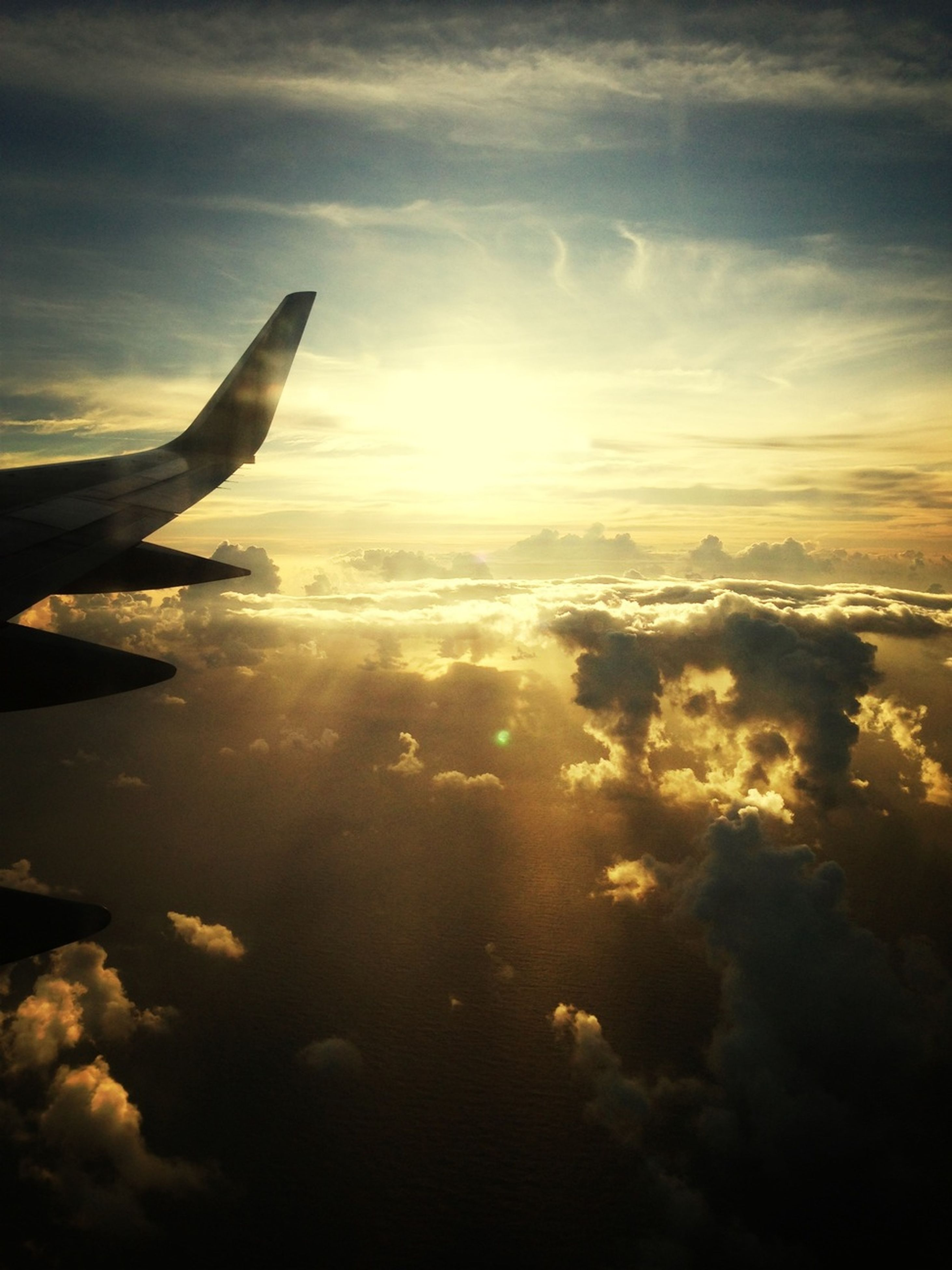 flying, sky, beauty in nature, scenics, cloud - sky, airplane, aerial view, aircraft wing, part of, sunset, nature, tranquil scene, cropped, air vehicle, mid-air, tranquility, cloudscape, transportation, cloud, sea