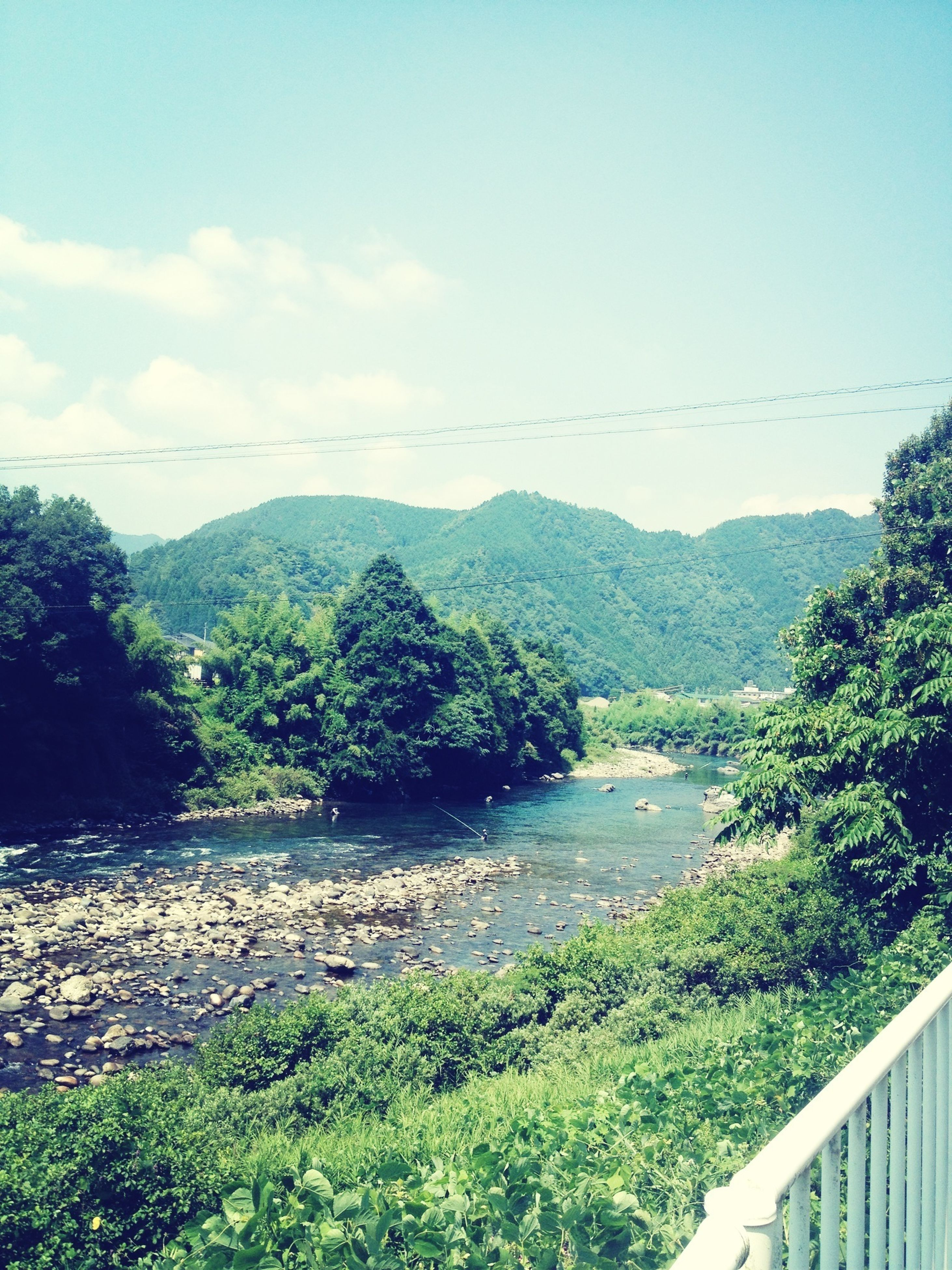 mountain, tranquil scene, scenics, sky, tranquility, mountain range, tree, water, beauty in nature, nature, landscape, plant, railing, river, green color, growth, non-urban scene, connection, idyllic, hill