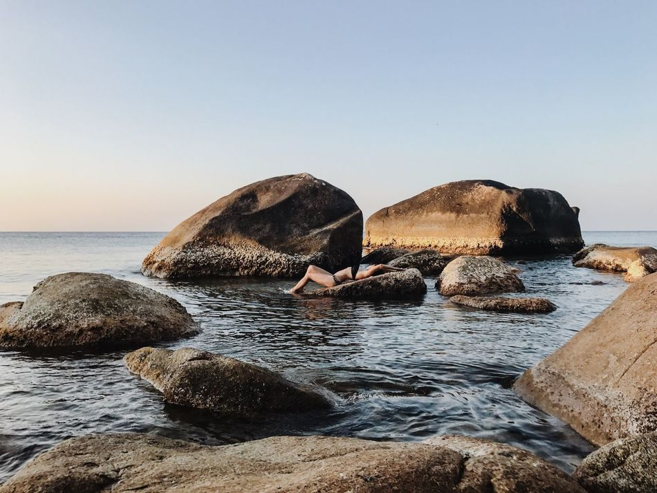 Sea Water Nature Rock - Object Clear Sky Horizon Over Water Beauty In Nature Rock Tranquility Tranquil Scene Scenics Outdoors One Woman Only Young Woman Lying Down Relaxation Vacations Leisure Activity Life Is A Beach Lifestyles Remote Rocky Coastline Beach Sky Golden Hour