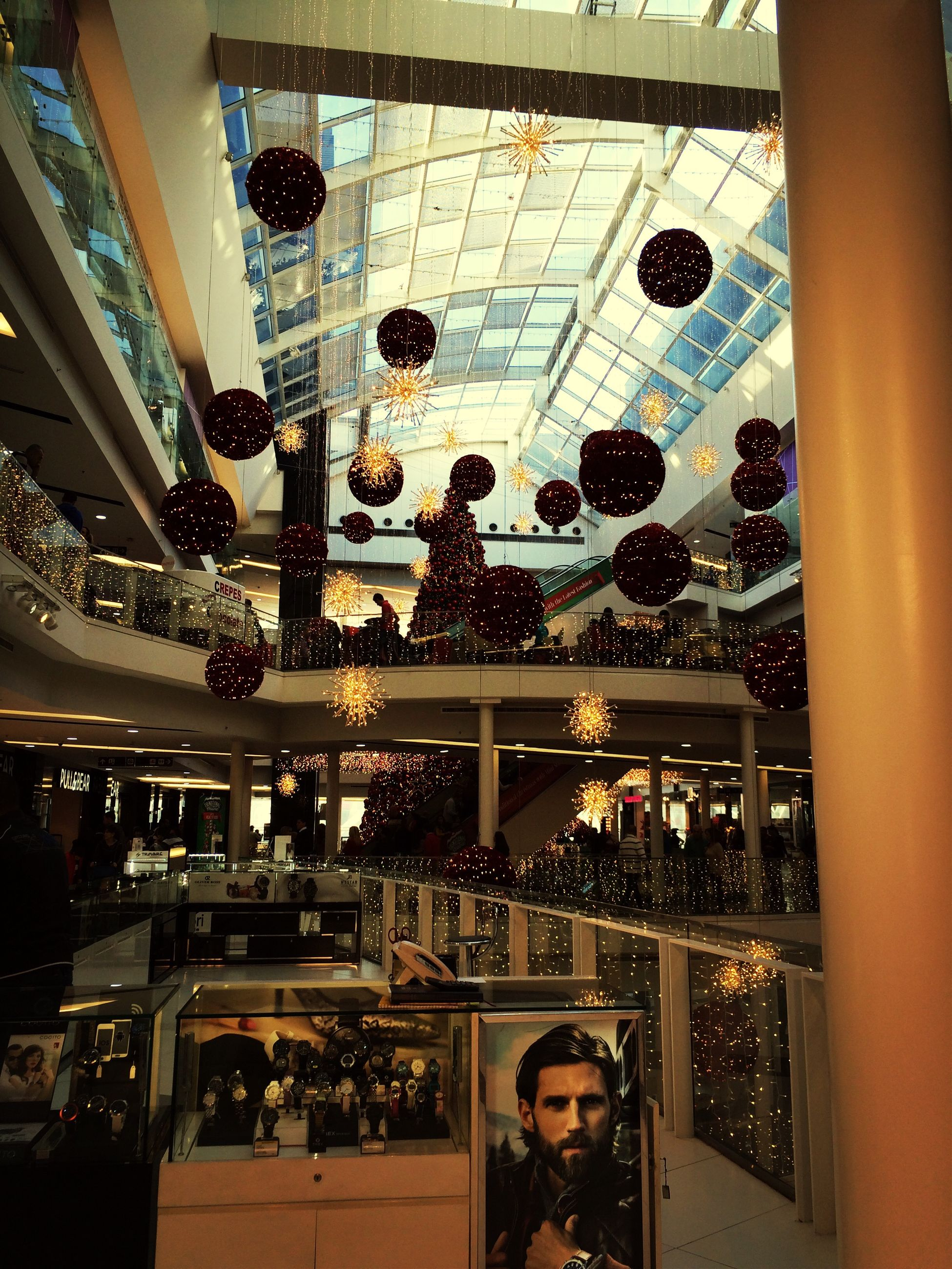 indoors, architecture, built structure, men, person, lifestyles, incidental people, leisure activity, ceiling, glass - material, large group of people, transportation, modern, shopping mall, window, city, city life, travel