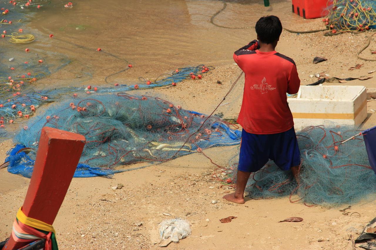 Fisherman Preparing Fishing Net On Beach
