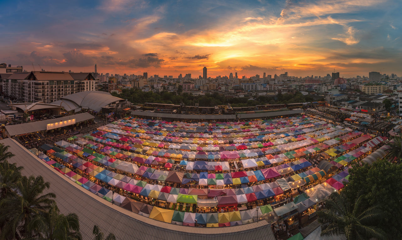 The sunset over Ratchada Train Night Market, Bangkok Thailand. The famous Bangkok night Market. and beautiful colour for tent canvas full market. Night bazaar. Bangkok Thailand. Business Food And Drink High Holiday Landmarks Market Panorama Ratchadapisek Square Tourist Building Cityscapes Cloud - Sky Colorful Decoration Landscapes Night People Scene Shop Skylines Tourism Tower Train