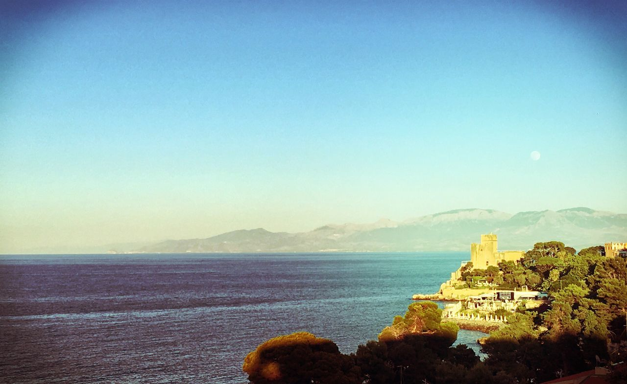sea, water, nature, beauty in nature, scenics, mountain, clear sky, no people, sky, tranquility, architecture, outdoors, blue, building exterior, day, horizon over water