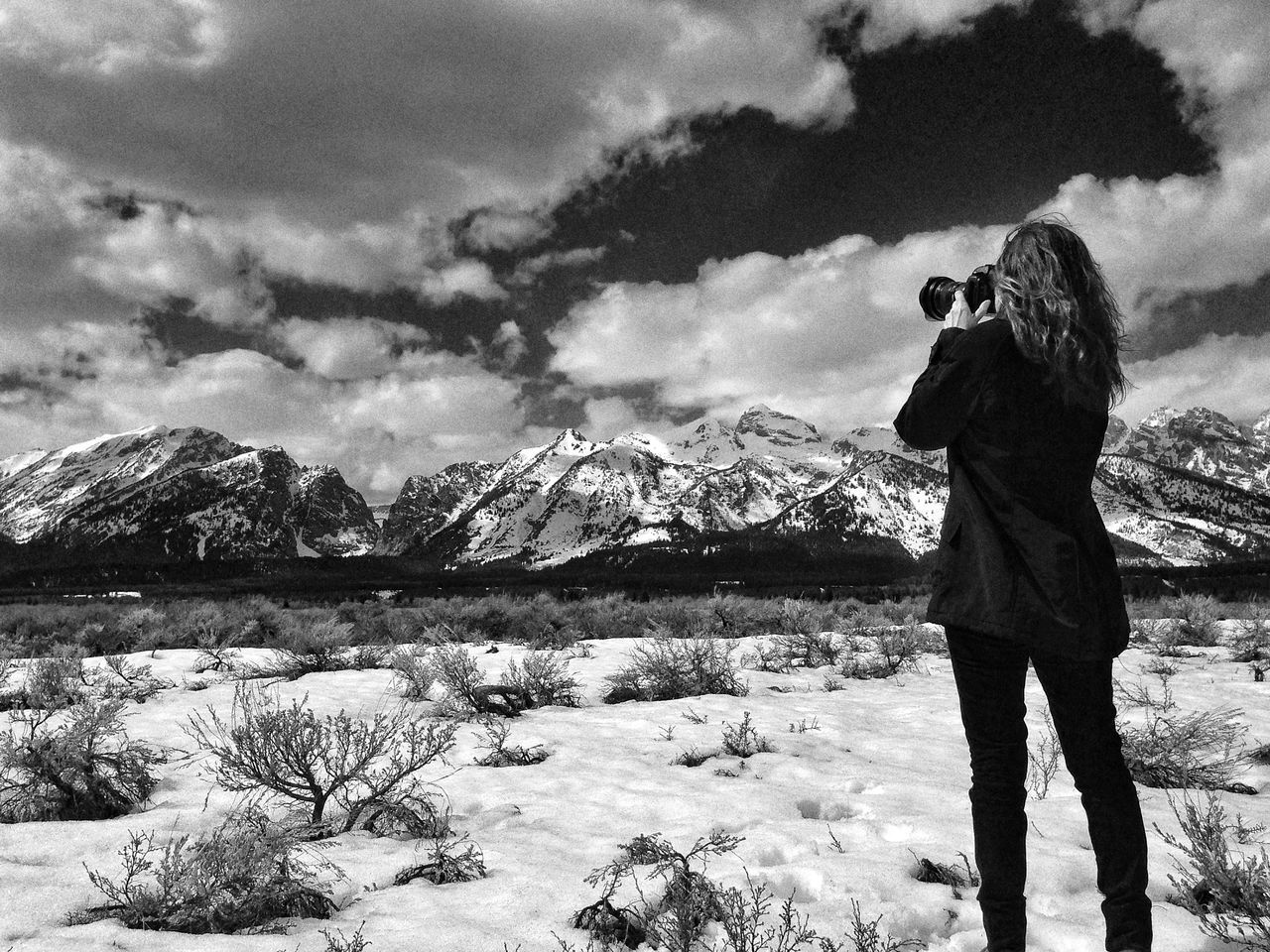 Rear View Of Woman Photographing Cloudy Sky Over Snowcapped Mountain