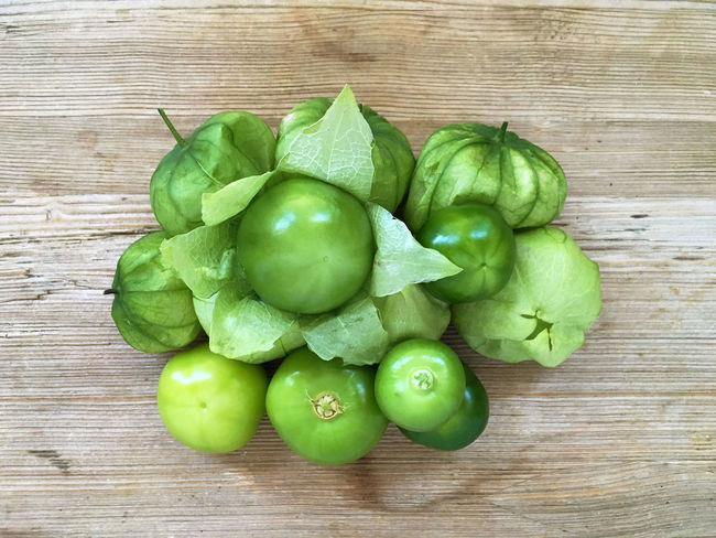Close-up Food Food And Drink Freshness Freshness Green Green Tomatoes Healthy Eating Healthy Eating; Ingredient Mexican Cuisine Mexican Food Mexican Husk Tomato No People Raw Food Ripe Table Tomate Tomatillo Tomatillos Tomato Tomatoes Vegetable Wooden Surface