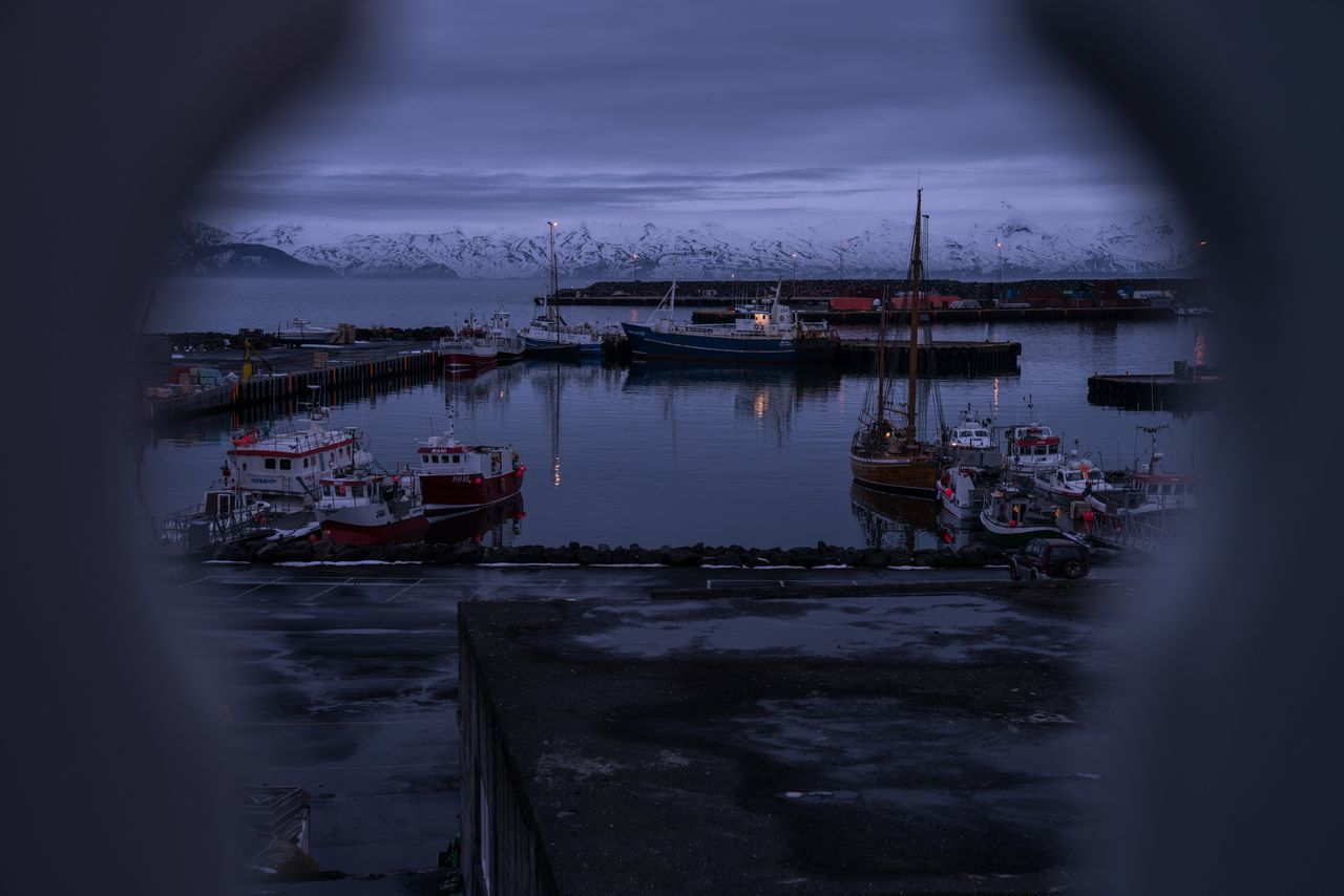 Peep. Nautical Vessel Water Boat Harbor Sea Outdoors Nature Beauty In Nature Iceland Memories Iceland_collection Iceland Iceland Trip Mountains Bay Husavik Peephole Nightphotography Night Lights Dusk Blue Hour Travel Photography Roadtrip Traveling Travel Destinations Harbour