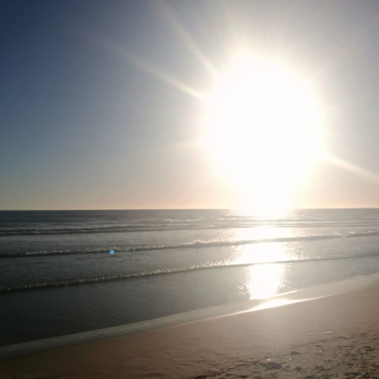 sea, sun, beach, sunbeam, beauty in nature, scenics, sunlight, nature, horizon over water, water, lens flare, tranquility, tranquil scene, bright, sand, idyllic, shore, sky, outdoors, sunset, brightly lit, no people, clear sky, day