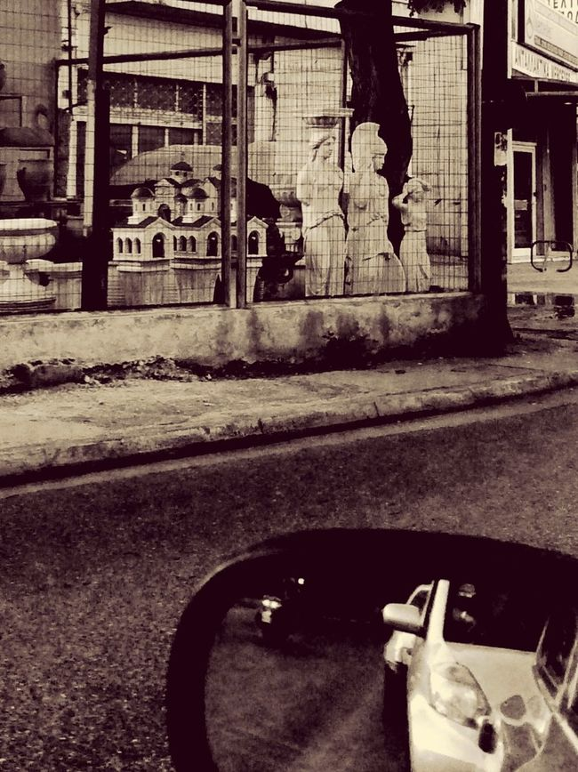 Cultural soup. Trapped goddesses overlooking car traffic. In The Car On The Way Home Kitsch Replicas Urban Life Athens Greece