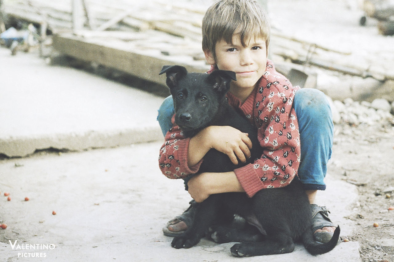 dog, one animal, pets, animal themes, domestic animals, looking at camera, real people, mammal, portrait, one person, sitting, cute, puppy, casual clothing, childhood, front view, full length, outdoors, smiling, holding, young animal, day, leisure activity, happiness, lifestyles, bonding, friendship, people