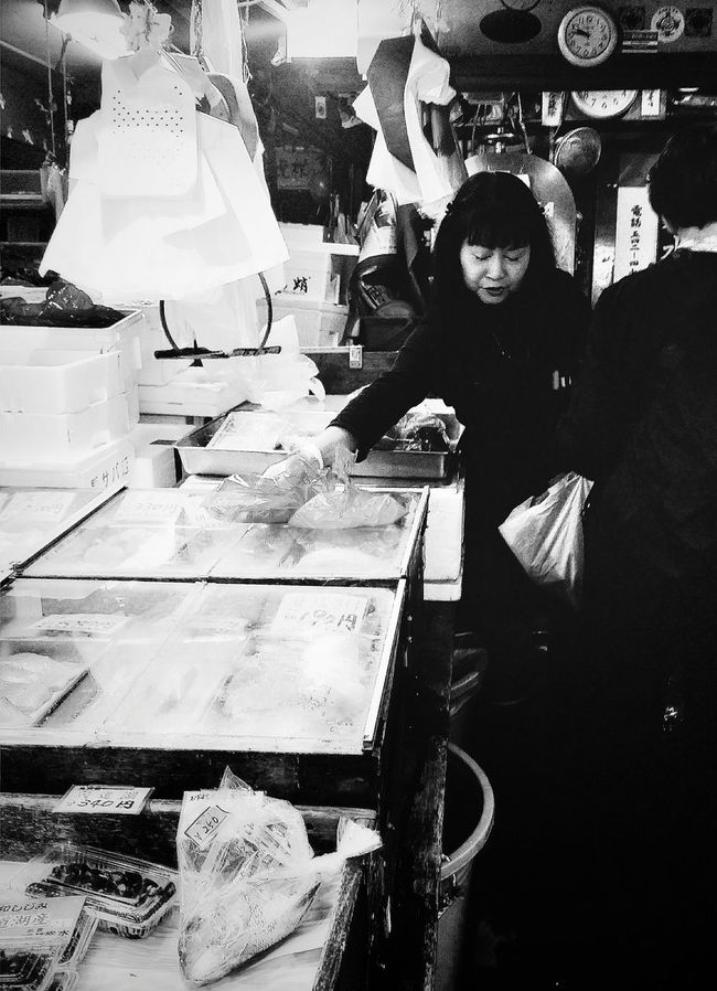 Tsukiji Fish Market is the largest Wholesale Fish and Seafood market in the world and also one of the biggest whole Food Markets of any kind. Fish Vendor Stall Tokyo Japan Travelphotography Streetphotography Bnw Bnwcollection Bnwphotographywholesale Bnw_captures Bnw_tokyo Blacknwhite You Won't Go Hungry In Tokyo!