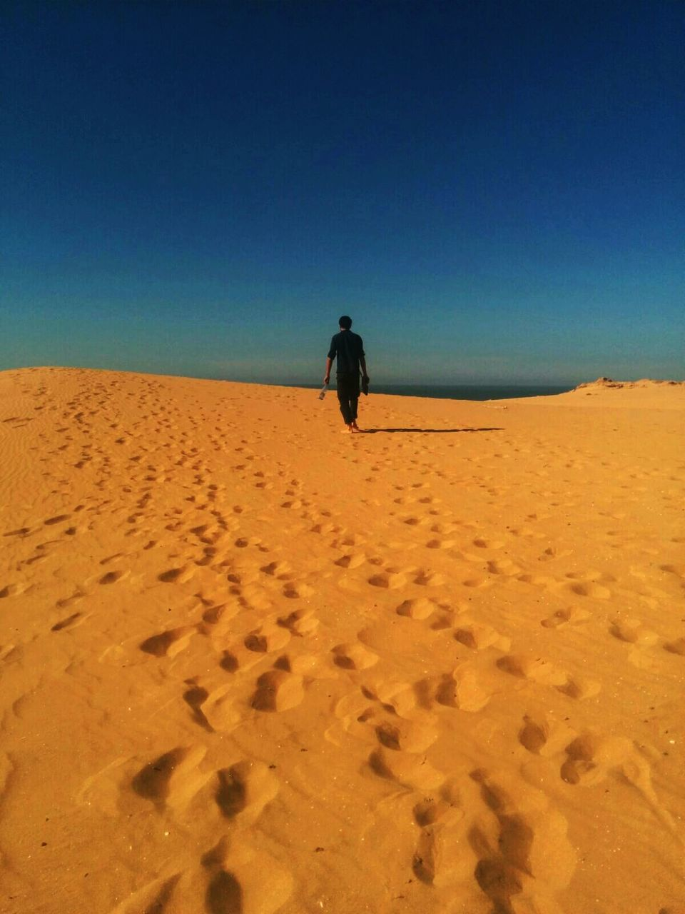 sand, one person, desert, arid climate, nature, landscape, clear sky, full length, sand dune, tranquil scene, walking, outdoors, real people, rear view, scenics, day, leisure activity, beach, sky, blue, lifestyles, vacations, women, beauty in nature, mammal, people