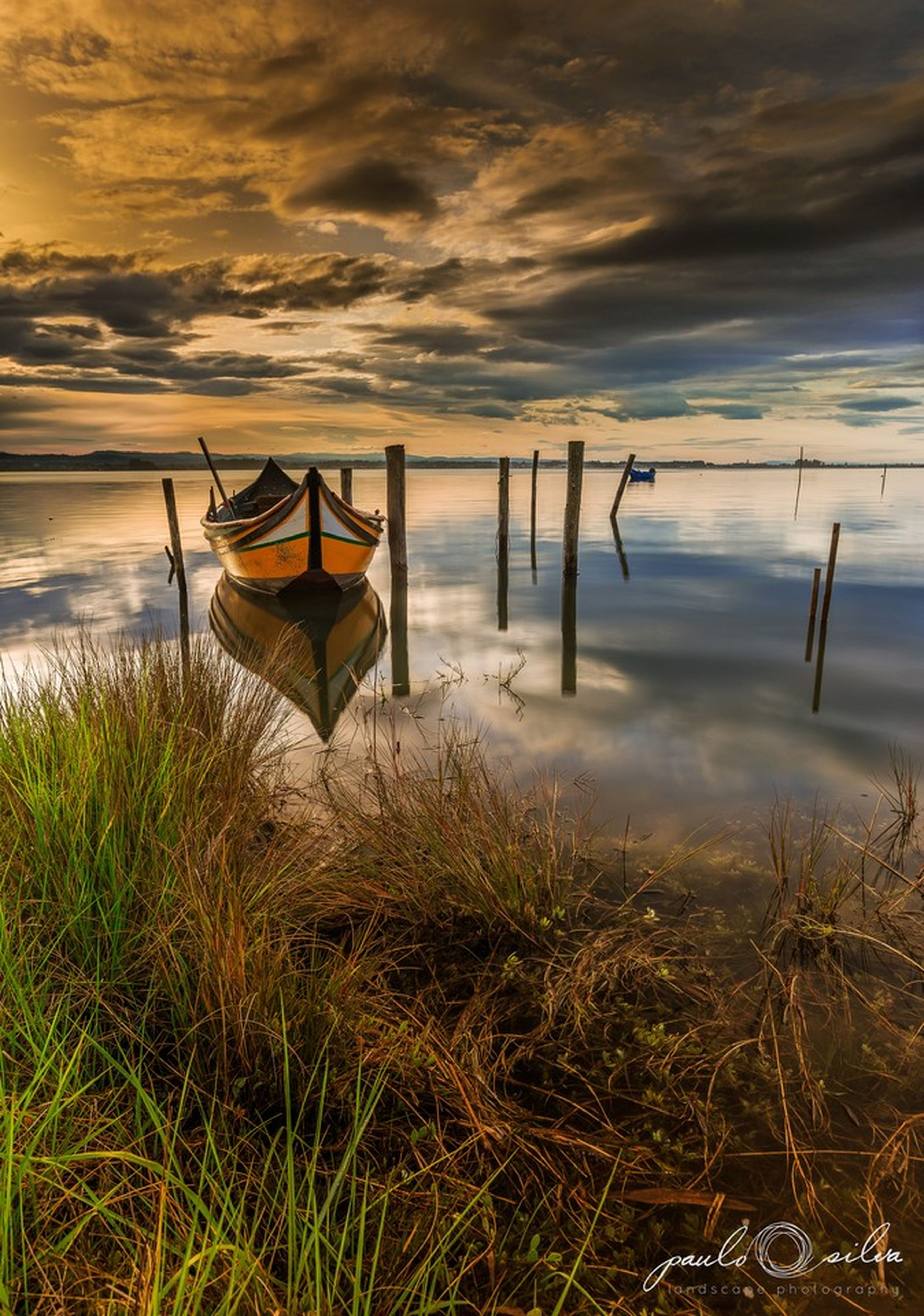 water, sky, grass, tranquility, cloud - sky, nautical vessel, nature, sea, boat, tranquil scene, beach, lake, cloud, beauty in nature, moored, shore, transportation, scenics, plant, cloudy