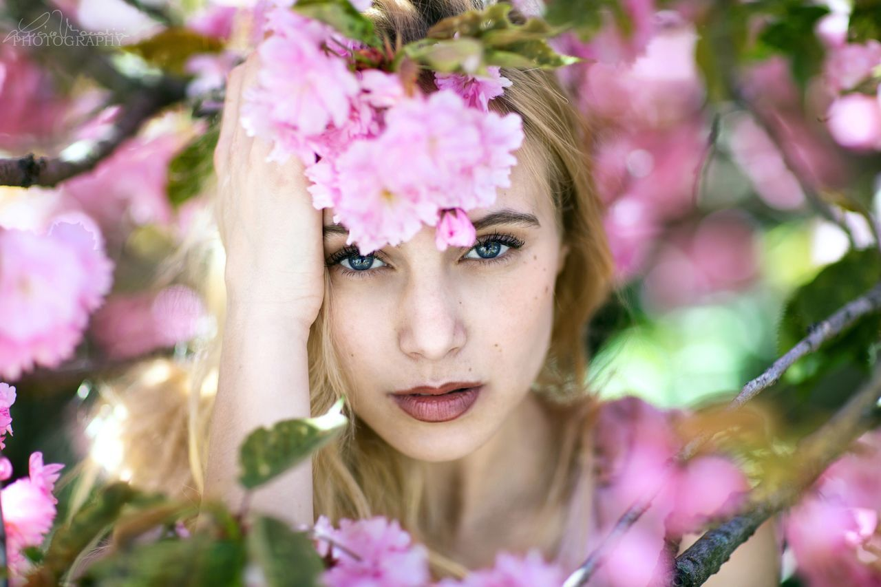 flower, pink color, young adult, beautiful woman, one person, young women, looking at camera, fragility, real people, headshot, front view, nature, day, focus on foreground, freshness, outdoors, portrait, close-up, plant, beauty in nature, flower head, people