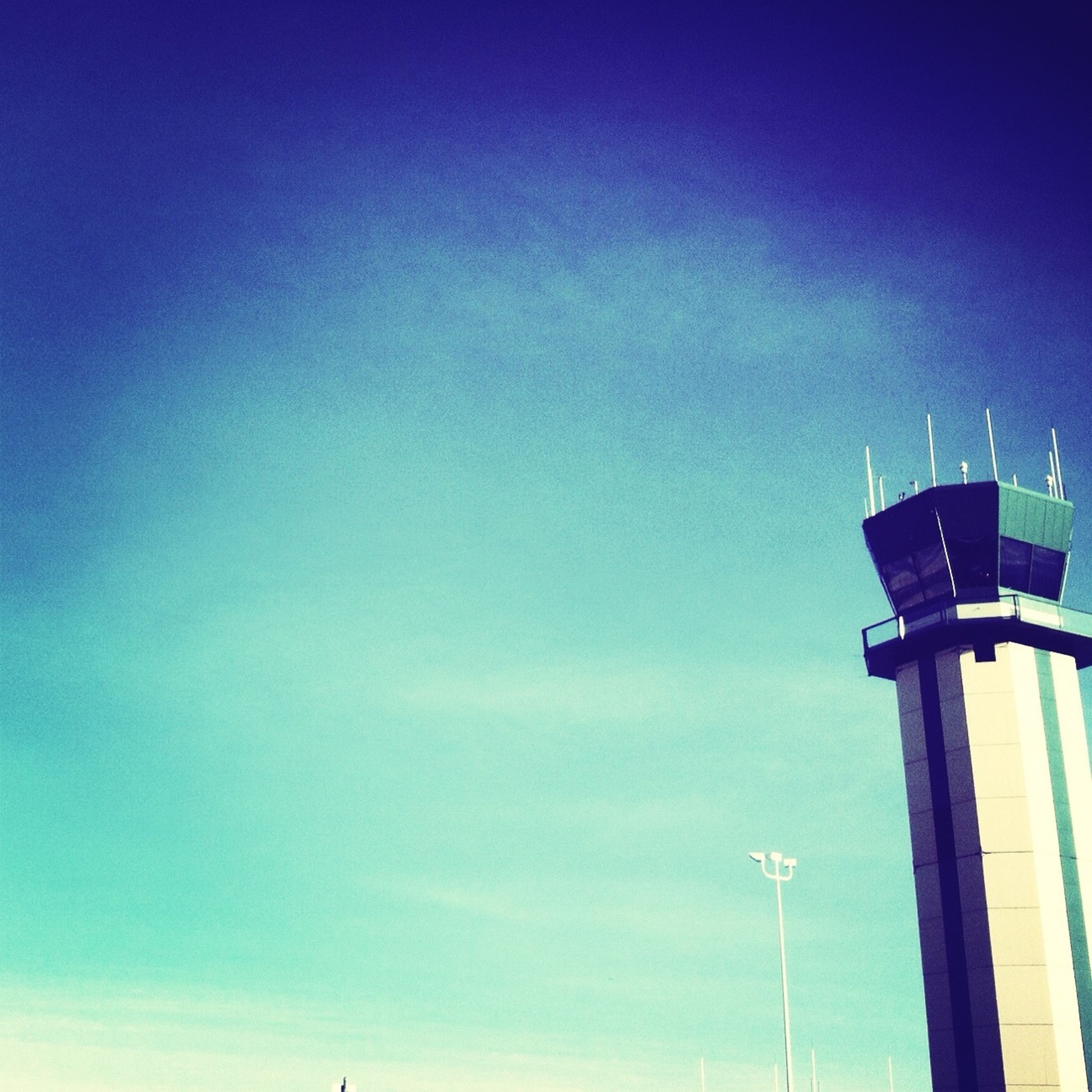 low angle view, blue, sky, built structure, street light, architecture, lighting equipment, copy space, pole, building exterior, tower, technology, tall - high, clear sky, communication, no people, outdoors, high section, guidance, day