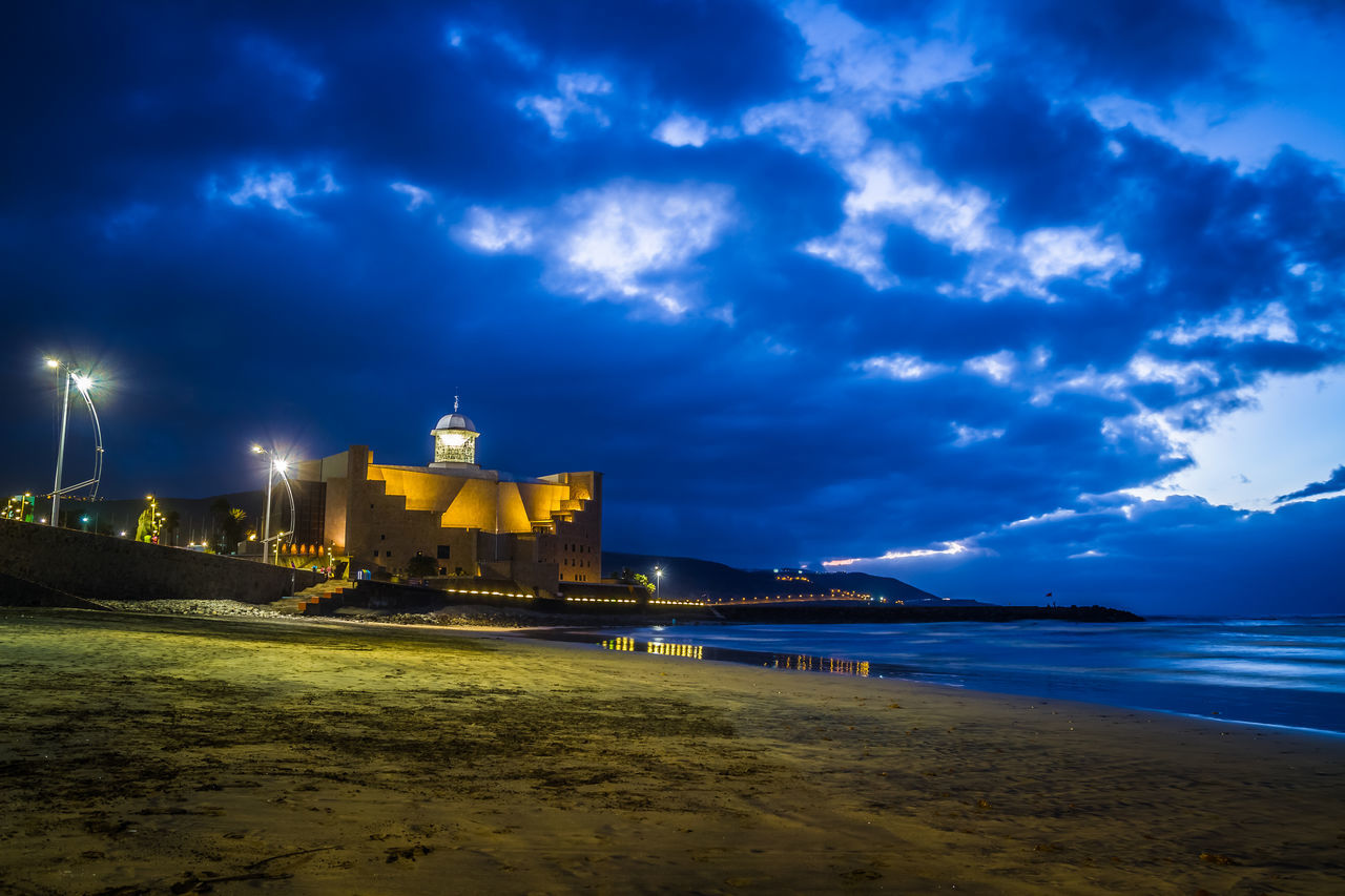 cloud - sky, sky, sea, architecture, built structure, water, nature, tourism, illuminated, travel destinations, religion, spirituality, beach, scenics, outdoors, building exterior, no people, night, place of worship, beauty in nature, horizon over water