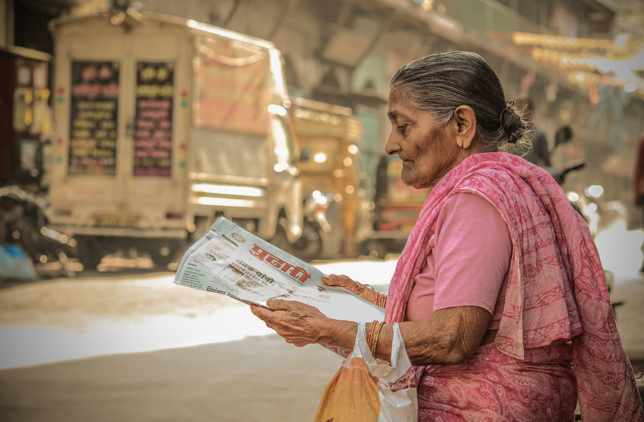real people, one person, focus on foreground, holding, travel, paper, outdoors, lifestyles, day, newspaper, close-up, adult, people