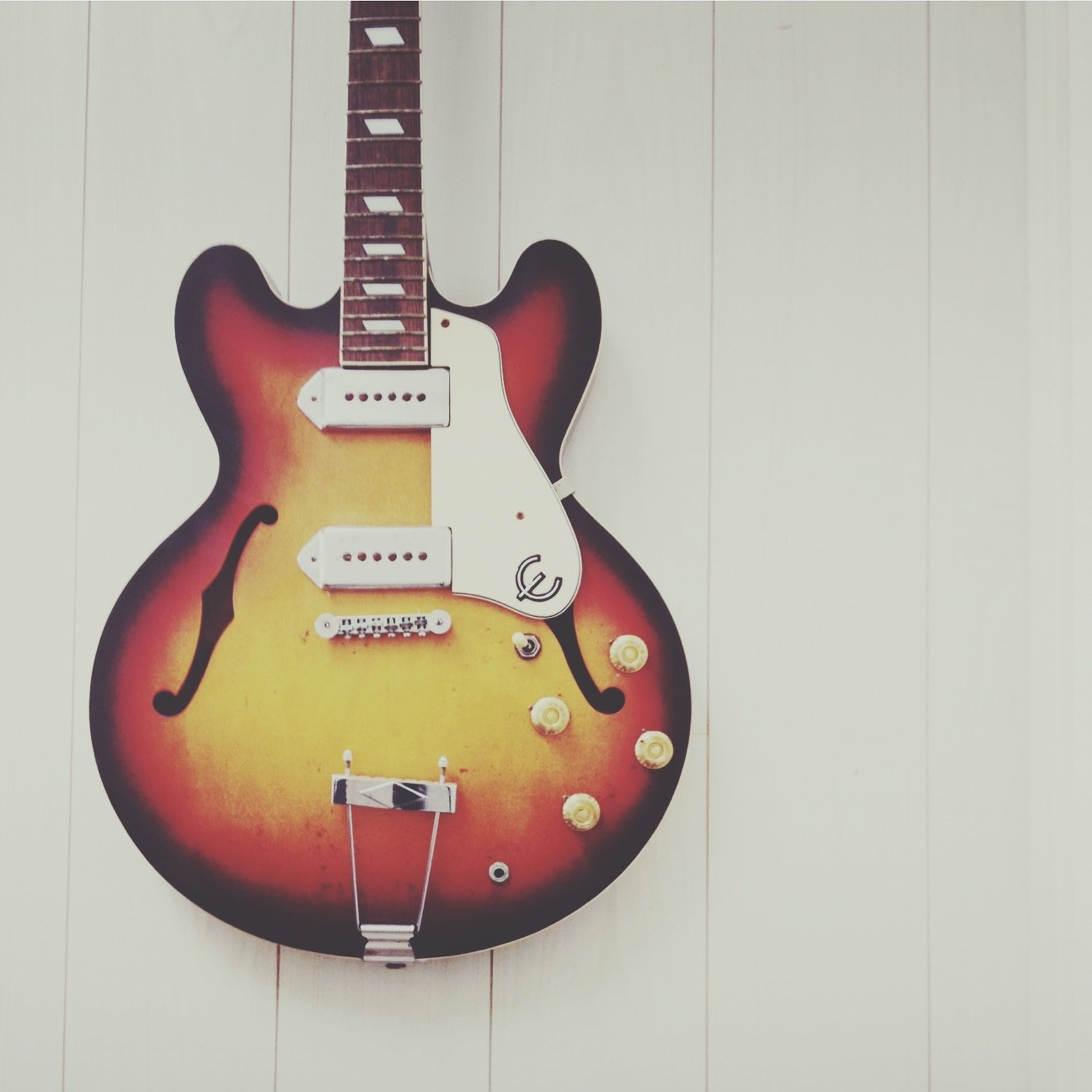 indoors, red, close-up, wall - building feature, single object, wood - material, door, still life, music, closed, no people, wall, musical instrument, metal, arts culture and entertainment, guitar, yellow, orange color, brown, communication