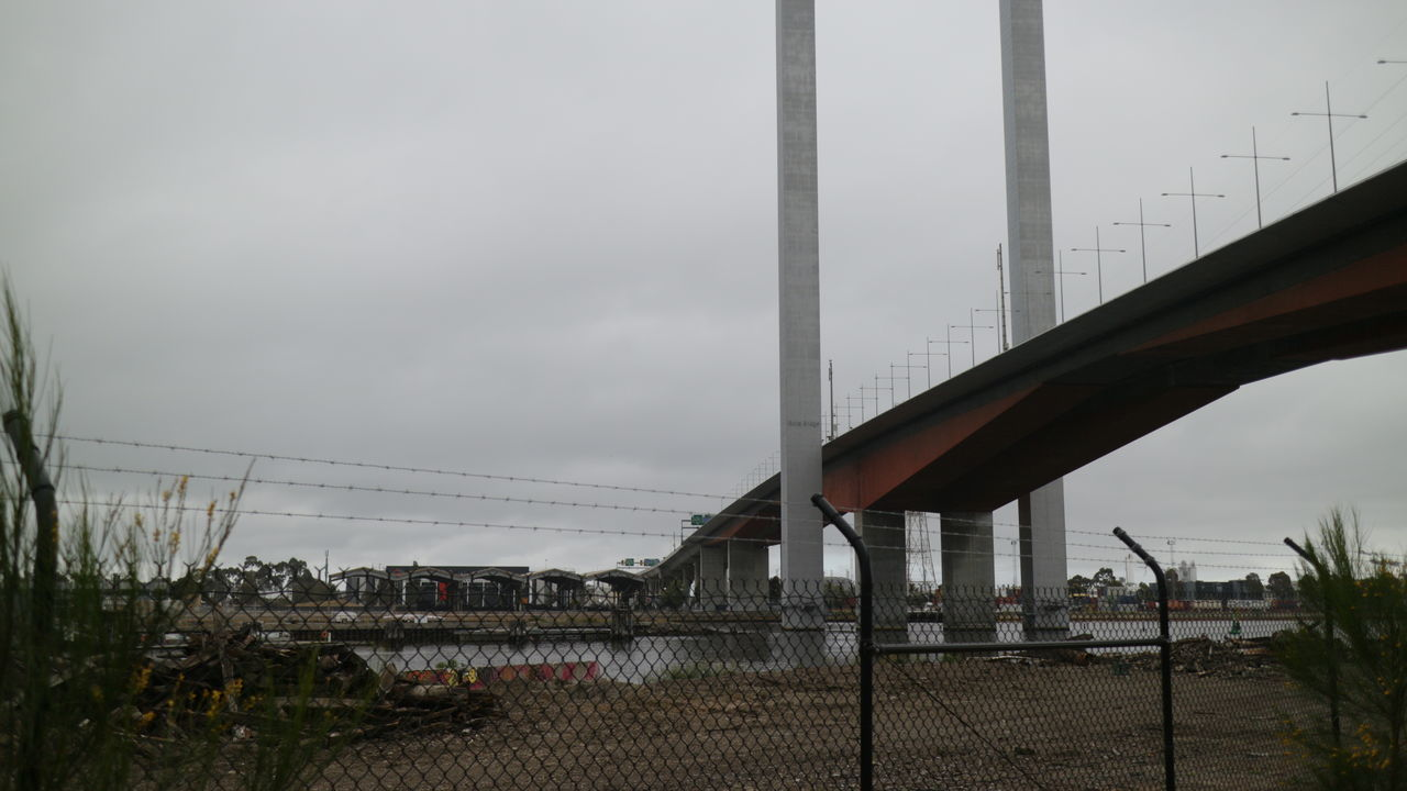 a view from ground level looking up at Melbourne's tollway and it's Bolte Bridge. Abandoned & Derelict Bolts Bridge Bridge - Man Made Structure Built Structure Connection Day Dingy Docklands Gray Sky Highway No People Outdoors Security Fence Sky Street Light Tollway Wasteland Adapted To The City