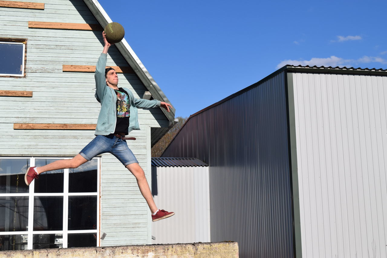 full length, young adult, real people, young women, built structure, architecture, lifestyles, outdoors, mid adult, day, one person, building exterior, casual clothing, leisure activity, beautiful woman, sunlight, low angle view, sky, clear sky, corrugated iron