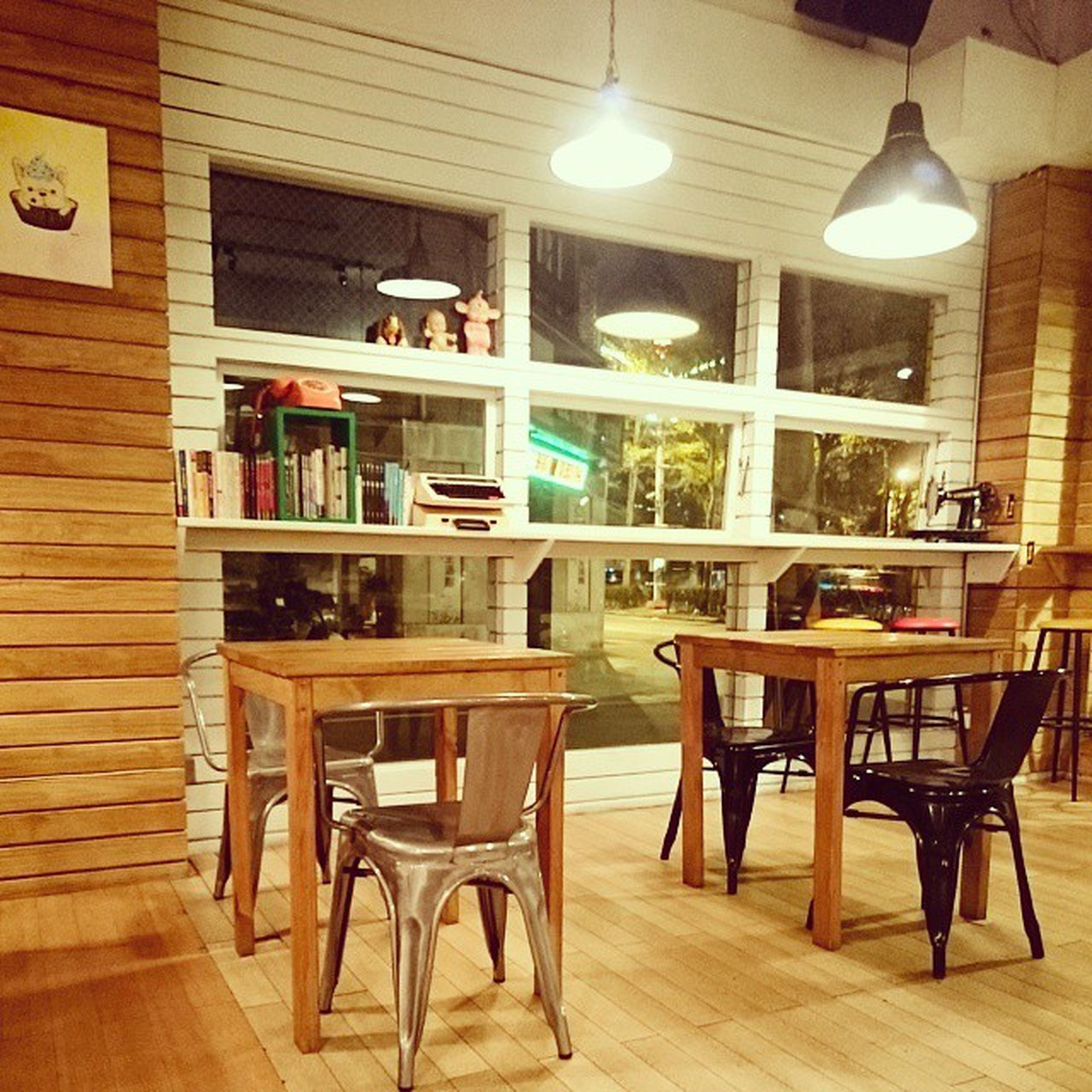 indoors, table, chair, empty, absence, restaurant, illuminated, furniture, place setting, arrangement, lighting equipment, electric lamp, cafe, window, home interior, architecture, wood - material, dining table, built structure, no people