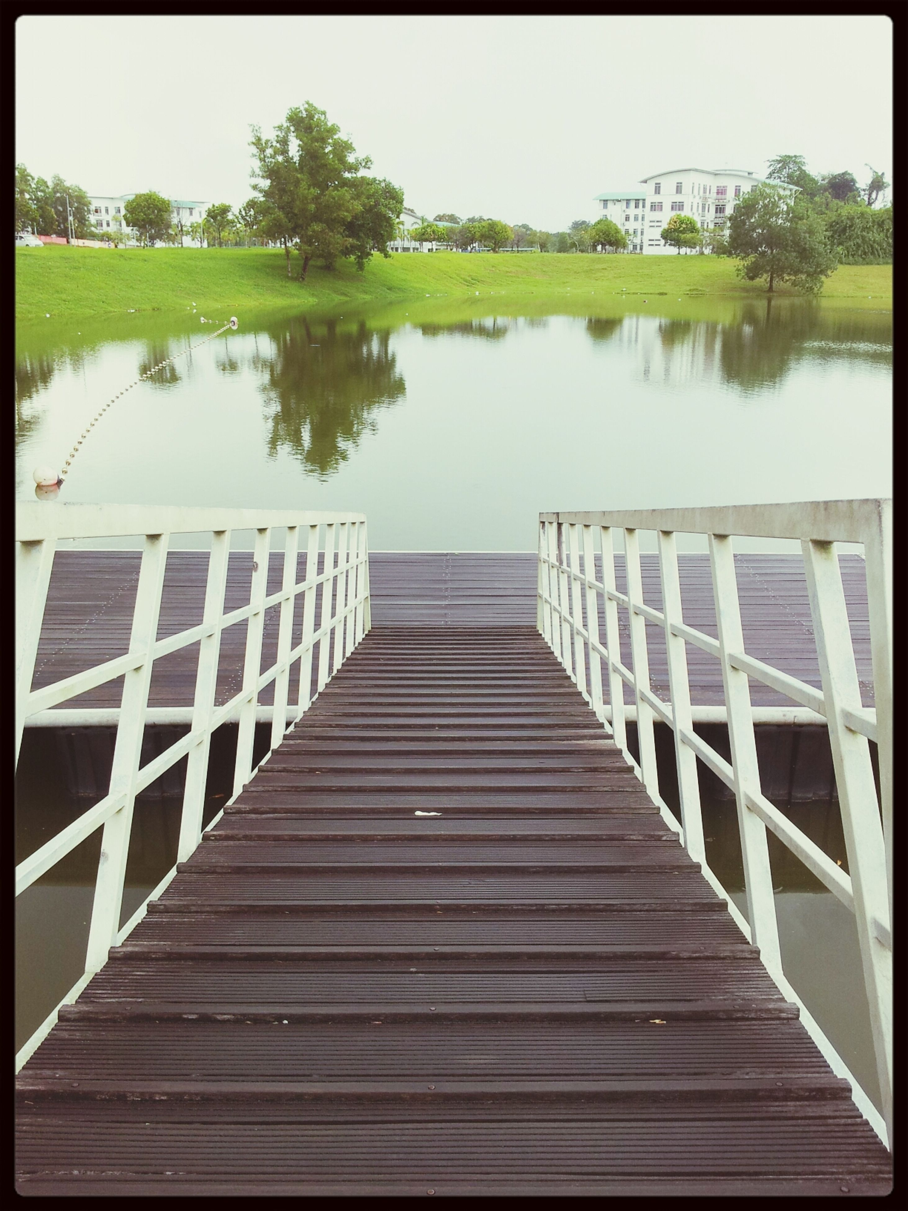 water, lake, transfer print, wood - material, pier, railing, built structure, reflection, wood, auto post production filter, tree, architecture, tranquility, footbridge, river, nature, day, sky, tranquil scene, jetty
