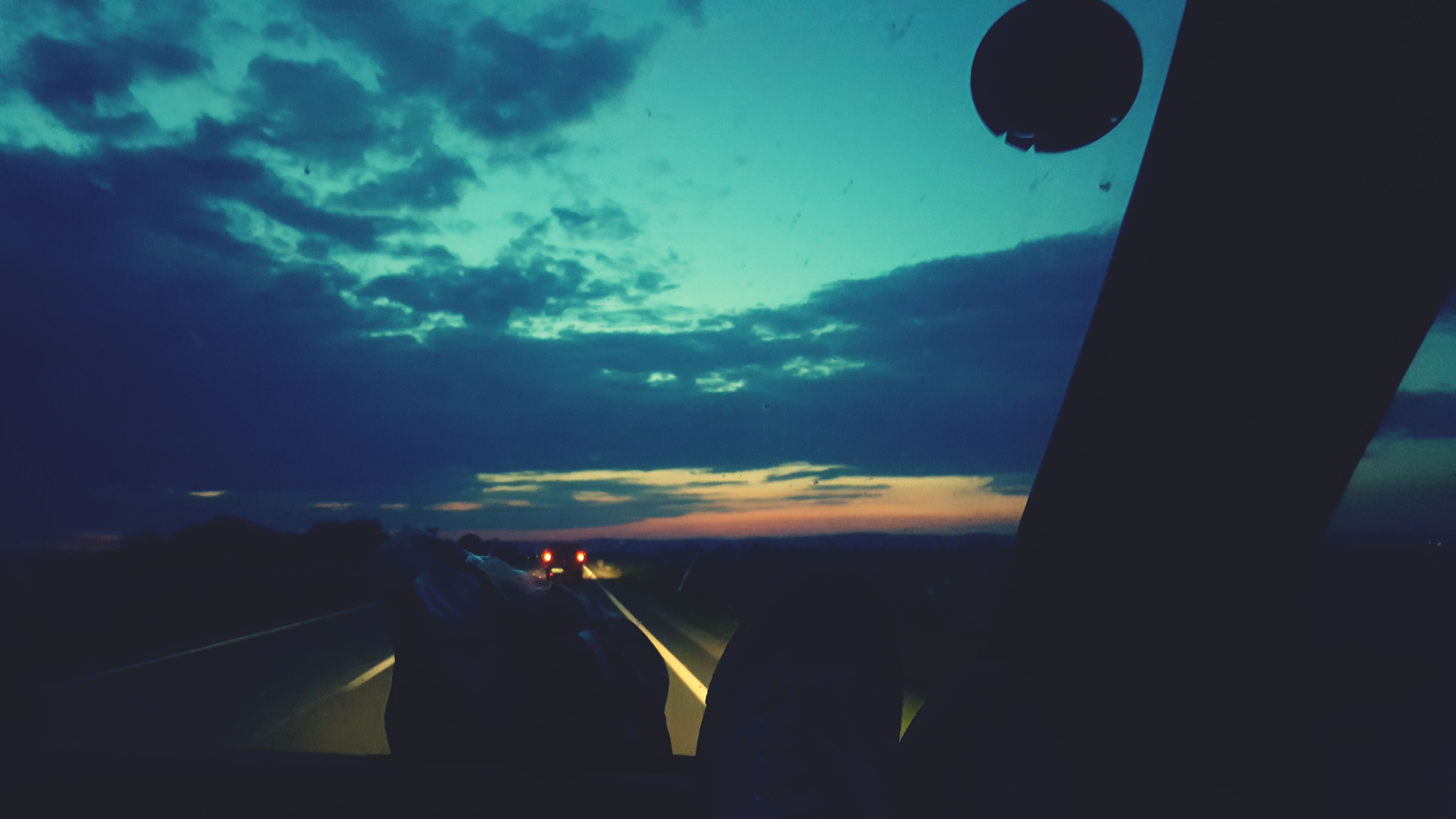 transportation, mode of transport, sky, vehicle interior, land vehicle, cloud - sky, sunset, windshield, on the move, journey, part of, road, cloud, cropped, nature, cloudy, beauty in nature, scenics, landscape, no people, outdoors, dark, blue