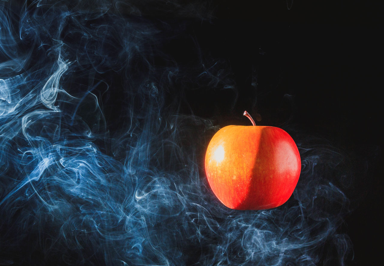Close-Up Of Apple And Smoke Against Black Background