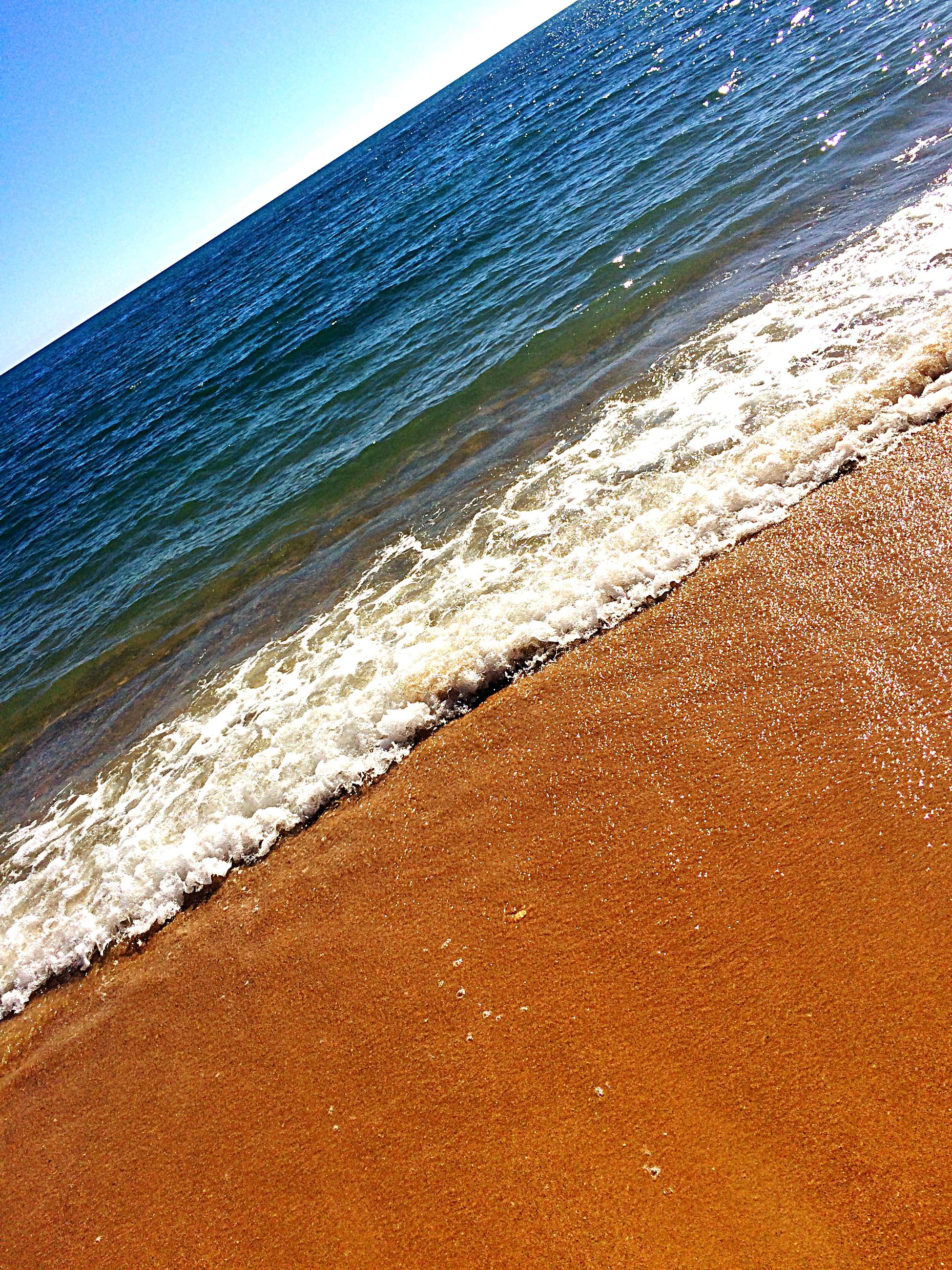 sea, water, beach, wave, surf, shore, horizon over water, beauty in nature, scenics, sand, tranquil scene, tranquility, nature, clear sky, coastline, blue, idyllic, sky, sunlight, outdoors