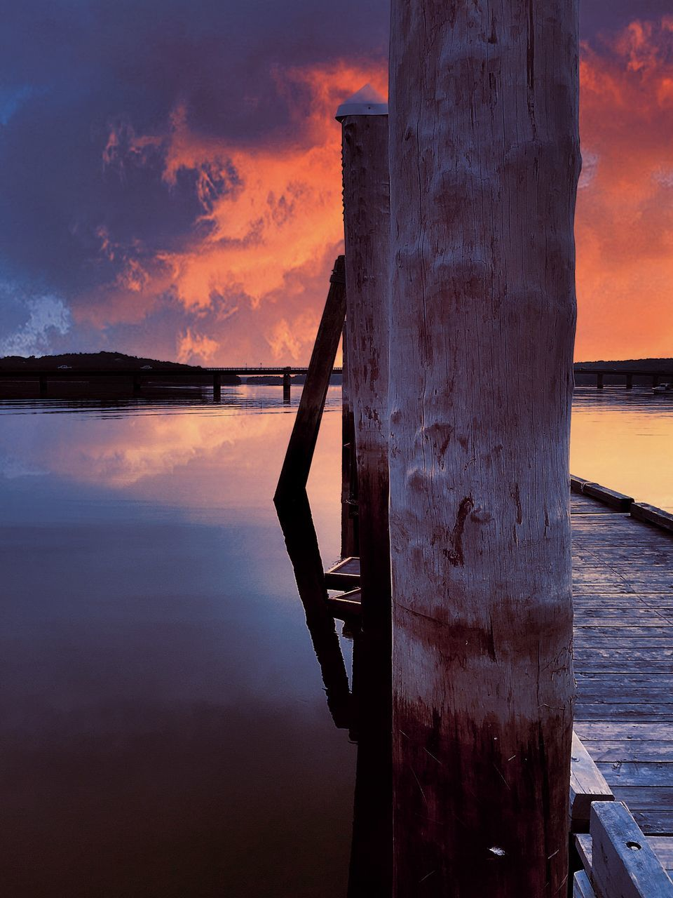 Wooden Post By Pier On Sea During Sunset