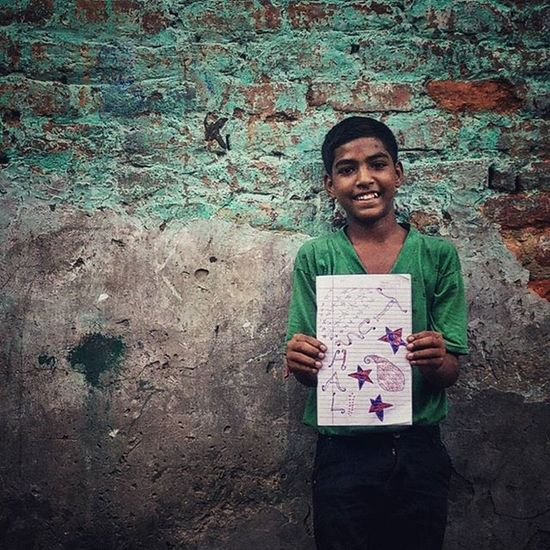 """13-year-old Tushal poses with a doodle sketched by him on a notebook. The doodle depicts his name. He feels blessed to be able to go to school and for being given a chance to be educated. He requested me to take a picture of him with his doodle when I was shooting in Katputli Nagar in Delhi, India. (4/5) Many a times, I have been approached by kids urging me to take pictures of them. They shout, """"Ek photo! Ek photo!"""" (One photo, one photo). The glee on their faces at the prospect of getting photographed makes me more than happy to oblige. After photographing the children, I realised that their expressions and their poses make the pictures special to me. Everydayeverywhere Everydayindia Dailylife Photojournalism Journalism Reportage Reportagespotlight Cityofcities Huffpostgram Everydayschool Indiaphotoproject Dfordelhi Sodelhi DelhiGram Onepluslife Oneplus2 Myfeatureshoot Delhi Newdelhi ASIA India"""