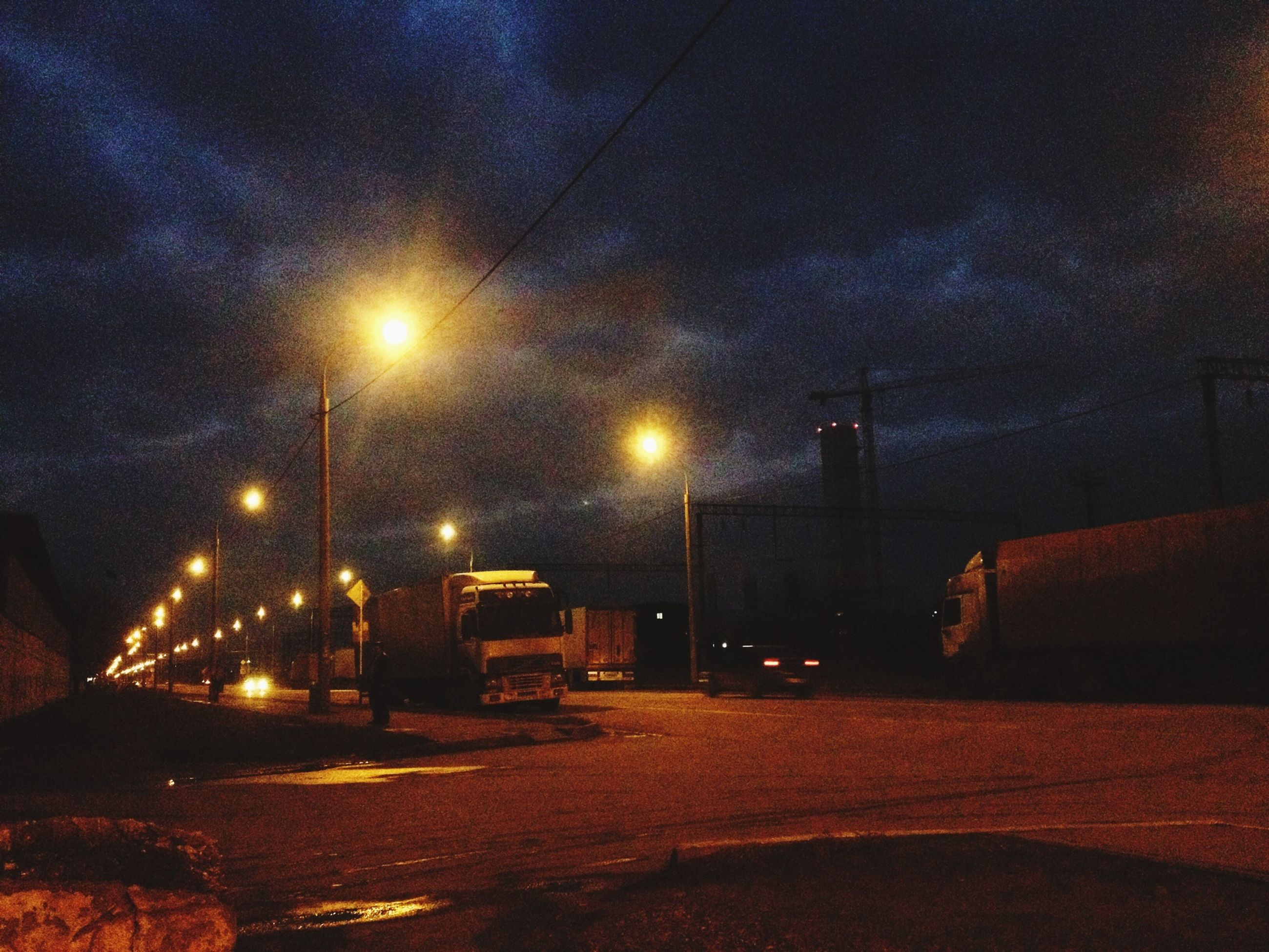 illuminated, street light, night, transportation, street, road, sky, lighting equipment, car, the way forward, land vehicle, built structure, architecture, building exterior, weather, mode of transport, cloud - sky, dusk, empty, outdoors