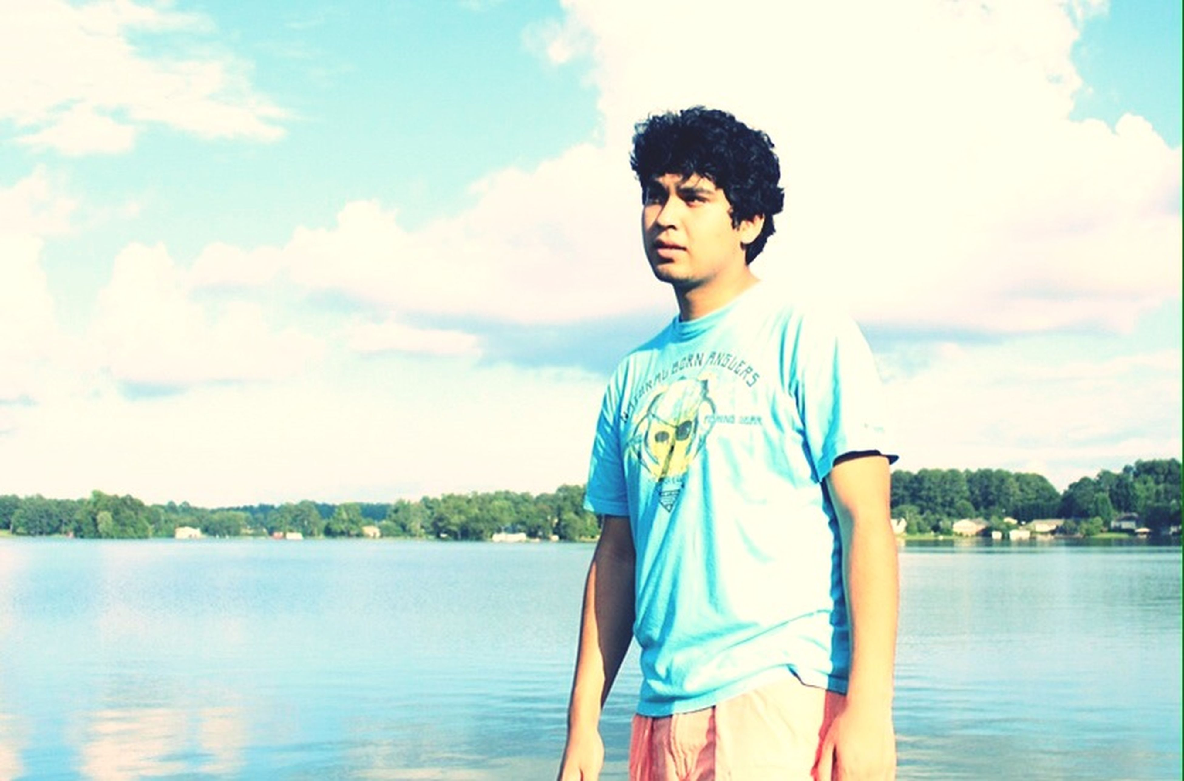 water, person, lifestyles, casual clothing, three quarter length, leisure activity, standing, sky, lake, waist up, young adult, front view, smiling, river, nature, childhood, young men, portrait