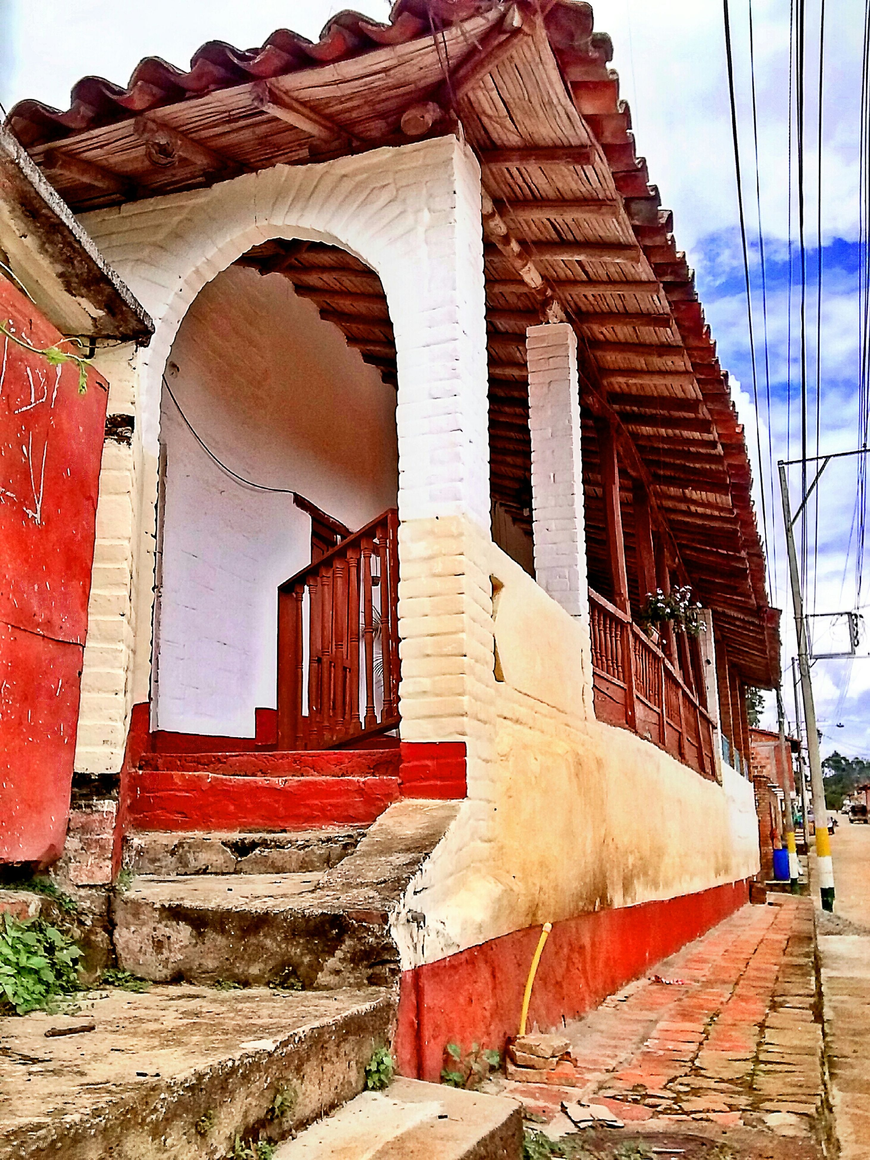 architecture, built structure, building exterior, brick wall, house, old, sky, low angle view, steps, sunlight, day, wall - building feature, outdoors, weathered, red, residential structure, building, no people, shadow, blue