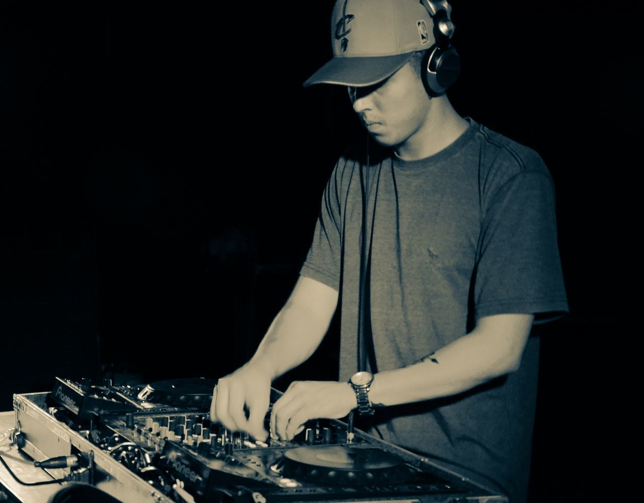 real people, one person, casual clothing, indoors, young adult, sound mixer, lifestyles, technology, night, dj, people