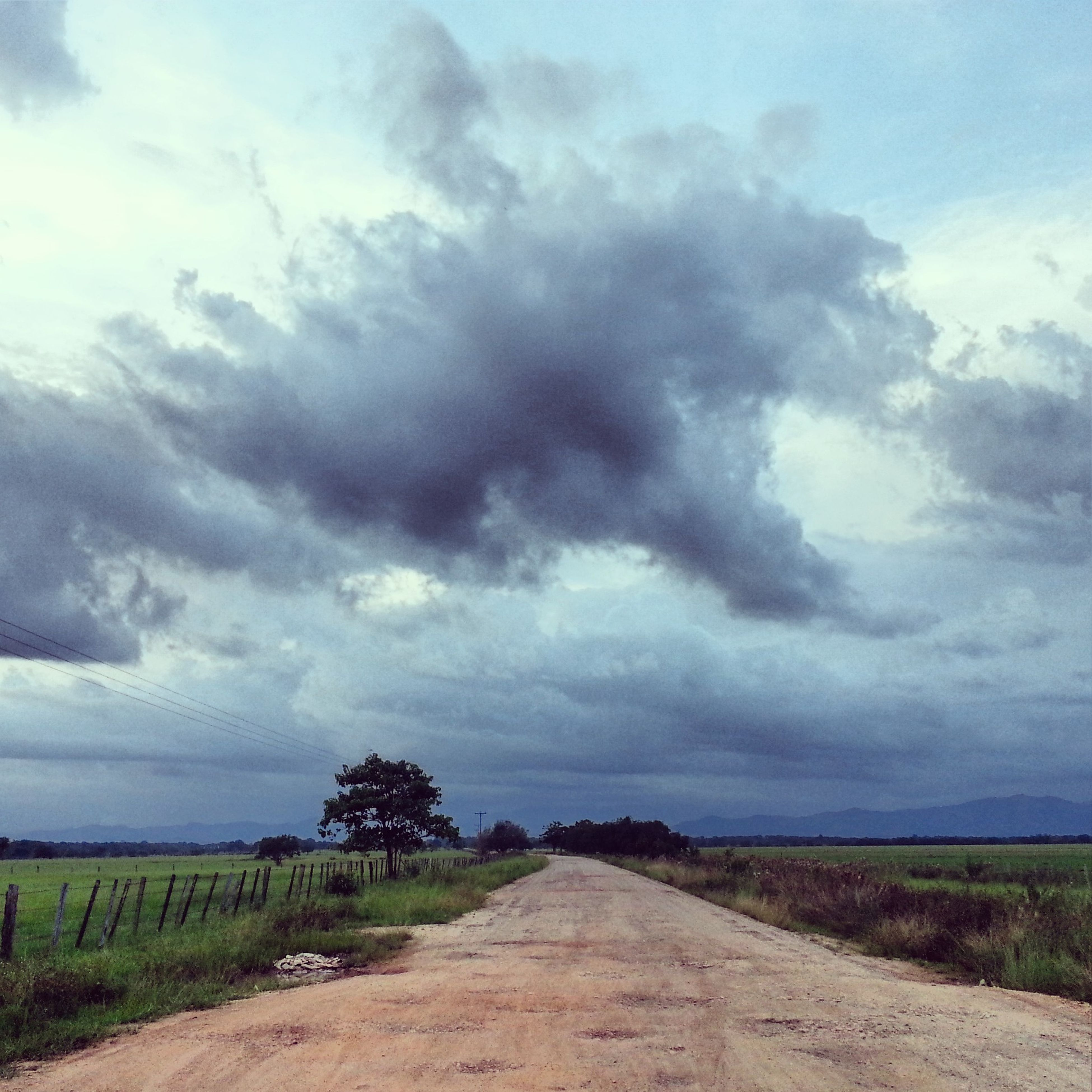 sky, cloud - sky, cloudy, tranquil scene, landscape, tranquility, the way forward, field, scenics, cloud, nature, beauty in nature, road, rural scene, dirt road, overcast, weather, grass, diminishing perspective, horizon over land