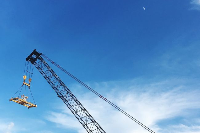 Crane in the sky Low Angle View Blue Development Sky Crane Day Cloud Progress Outdoors High Section No People High Up Carefree Construction Equipment Monument Flying Tall Multi Colored Bermuda Moon Container Port Container Crane