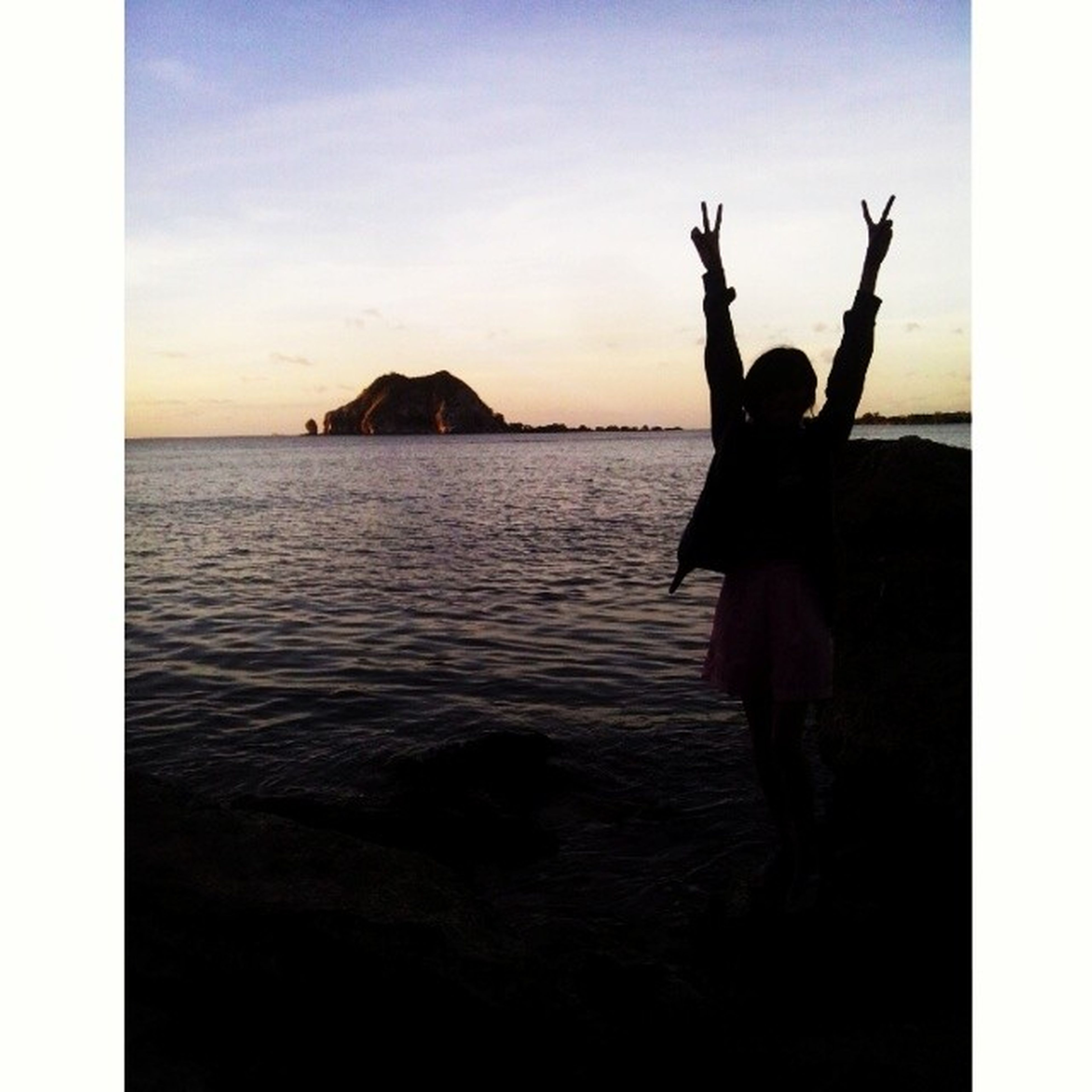 sea, transfer print, water, sky, auto post production filter, horizon over water, human representation, leisure activity, silhouette, lifestyles, full length, statue, arms raised, sculpture, sunset, mid-air, art and craft, scenics