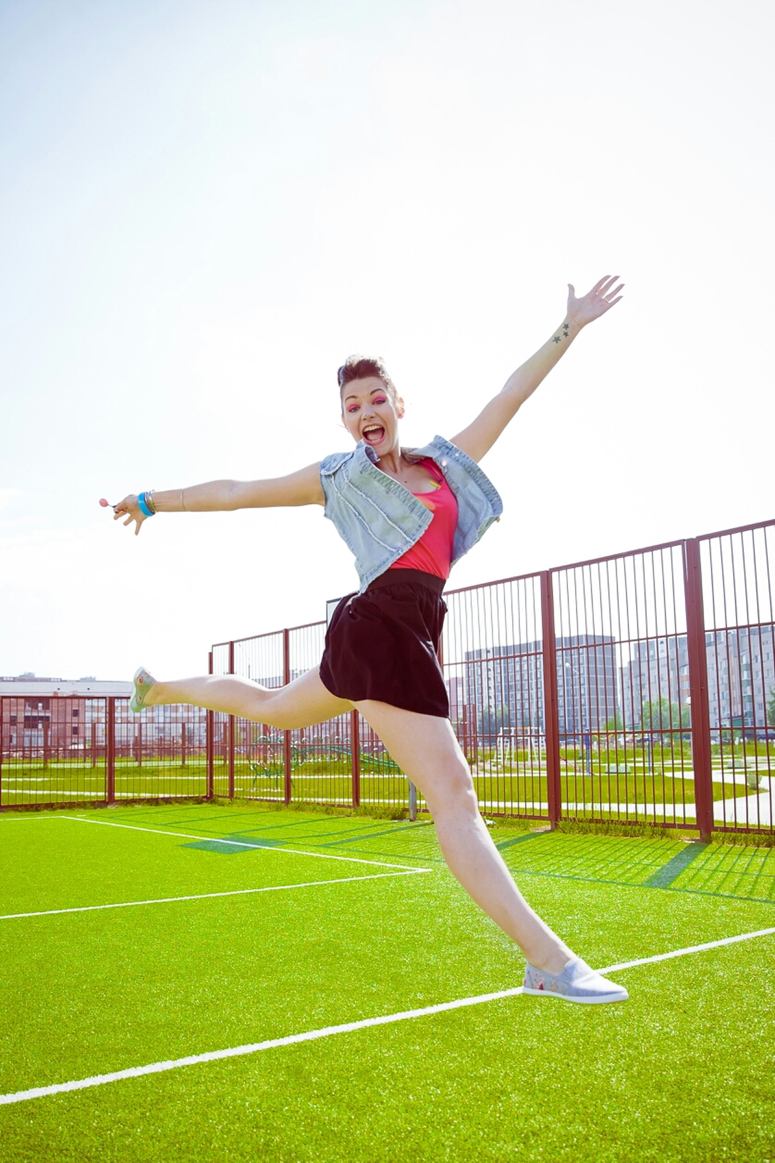 full length, lifestyles, leisure activity, casual clothing, person, grass, young adult, mid-air, arms outstretched, standing, fun, enjoyment, happiness, clear sky, front view, childhood, park - man made space, smiling