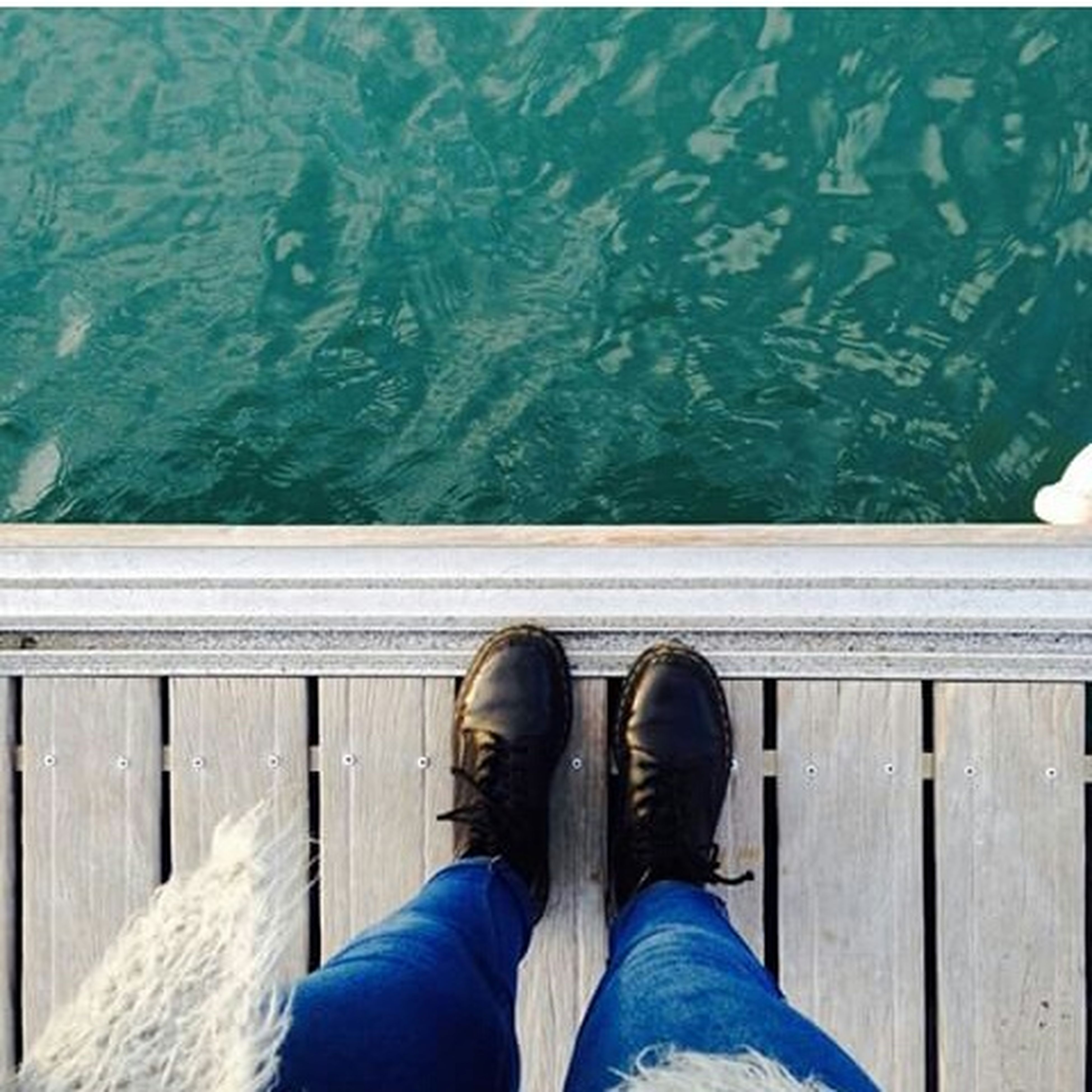 low section, person, personal perspective, shoe, human foot, lifestyles, standing, jeans, footwear, blue, relaxation, men, leisure activity, wood - material, sitting, pier, legs crossed at ankle
