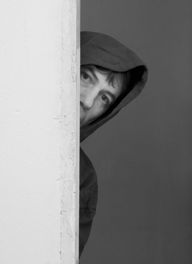 man in hood Concept Curious Doorway Fear Hiding Hood Looking Lurking Man Mysterious Mystery Observing Peeking Peeping Person Secrecy Sneaking Spying Suspect Suspicious