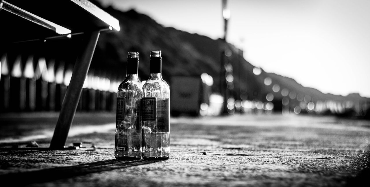 Up Close Street Photography Morning After Wine Bottles Bench Beach Seafront Empty