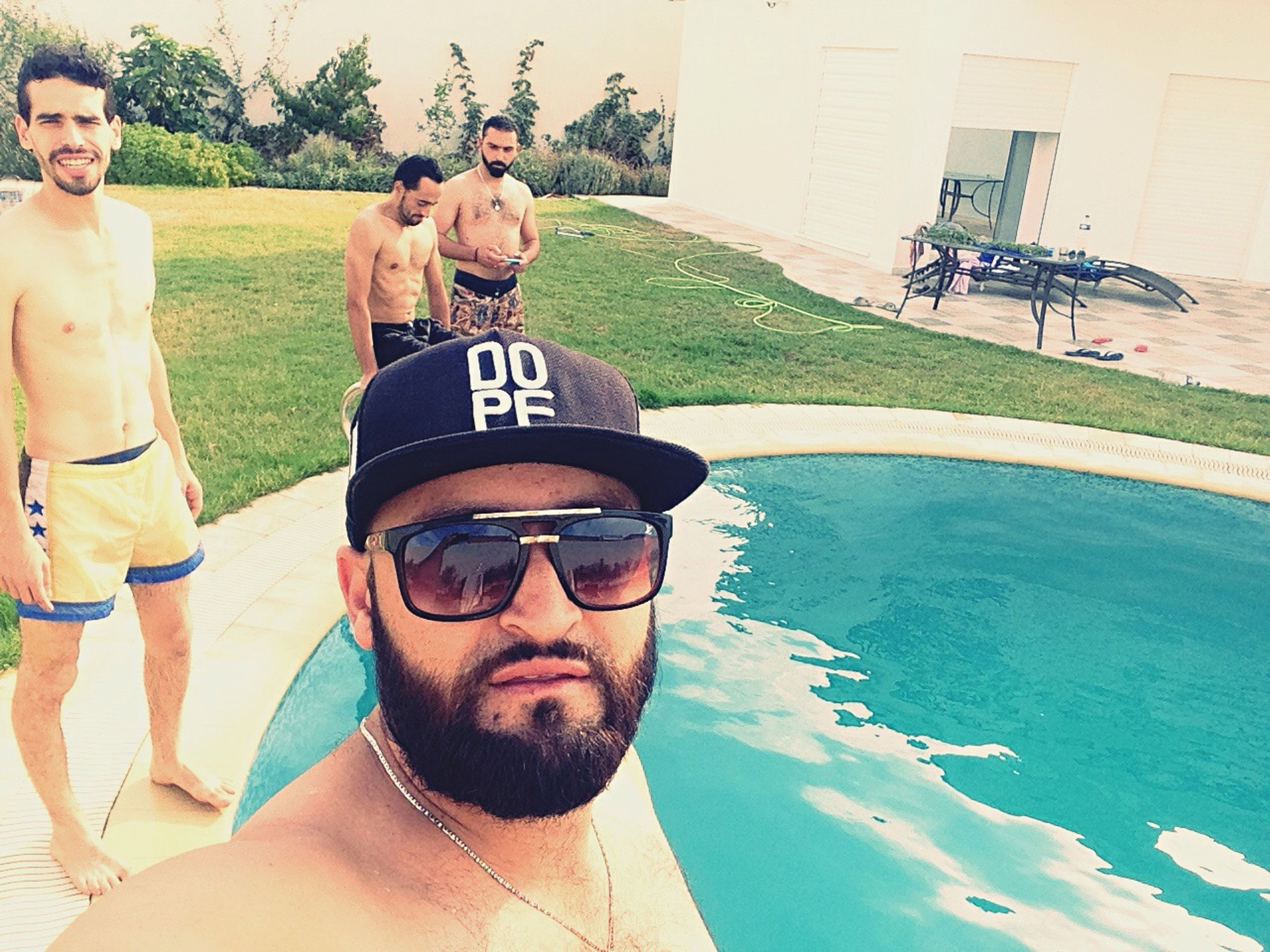 real people, mid adult men, sunglasses, leisure activity, outdoors, young men, day, lifestyles, young adult, tree, water, swimming pool, nature, togetherness, mammal