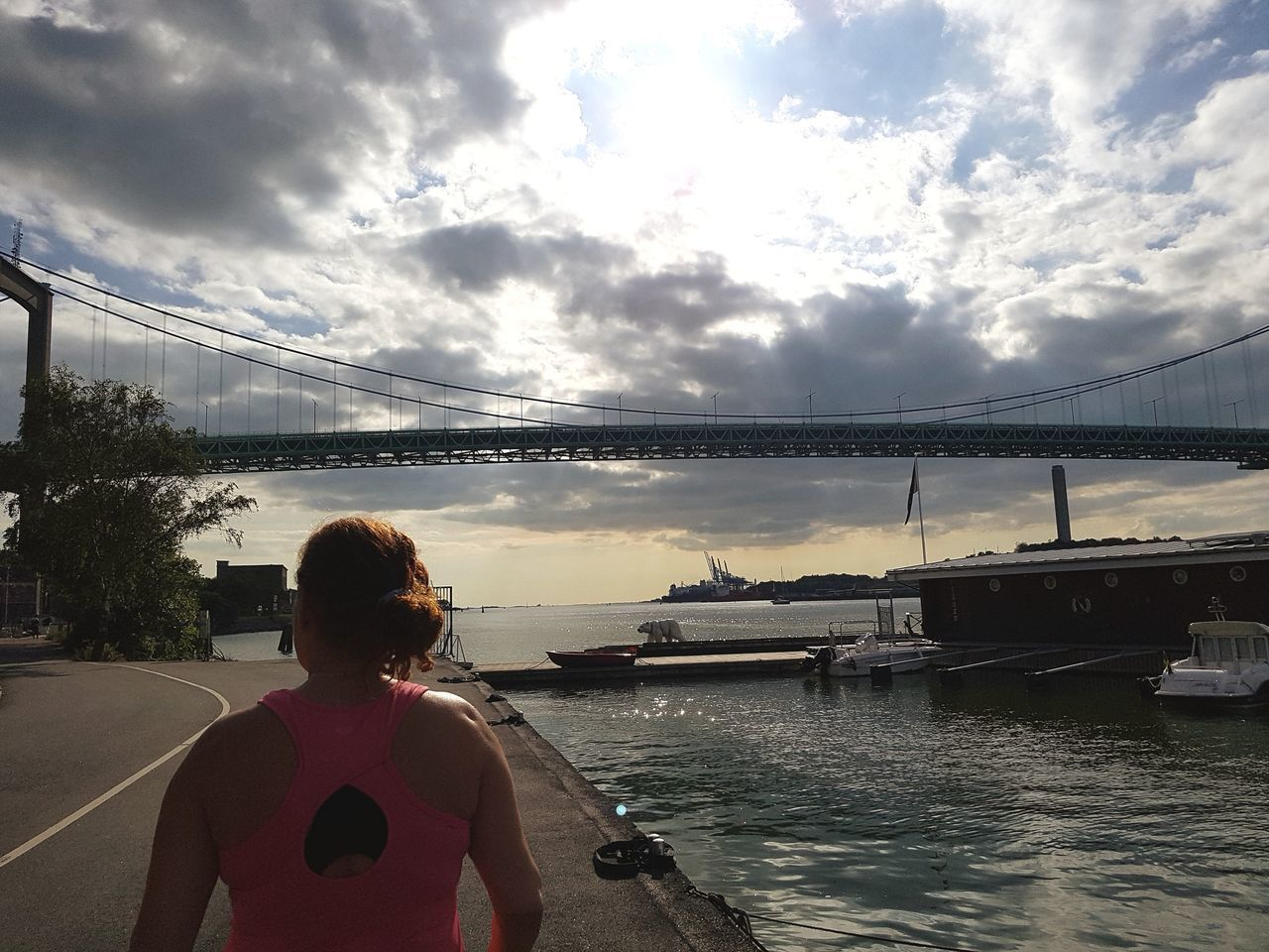 rear view, cloud - sky, bridge - man made structure, sky, real people, one person, water, connection, river, transportation, women, lifestyles, built structure, architecture, outdoors, leisure activity, suspension bridge, day, standing, sunset, nautical vessel, nature, adult, people