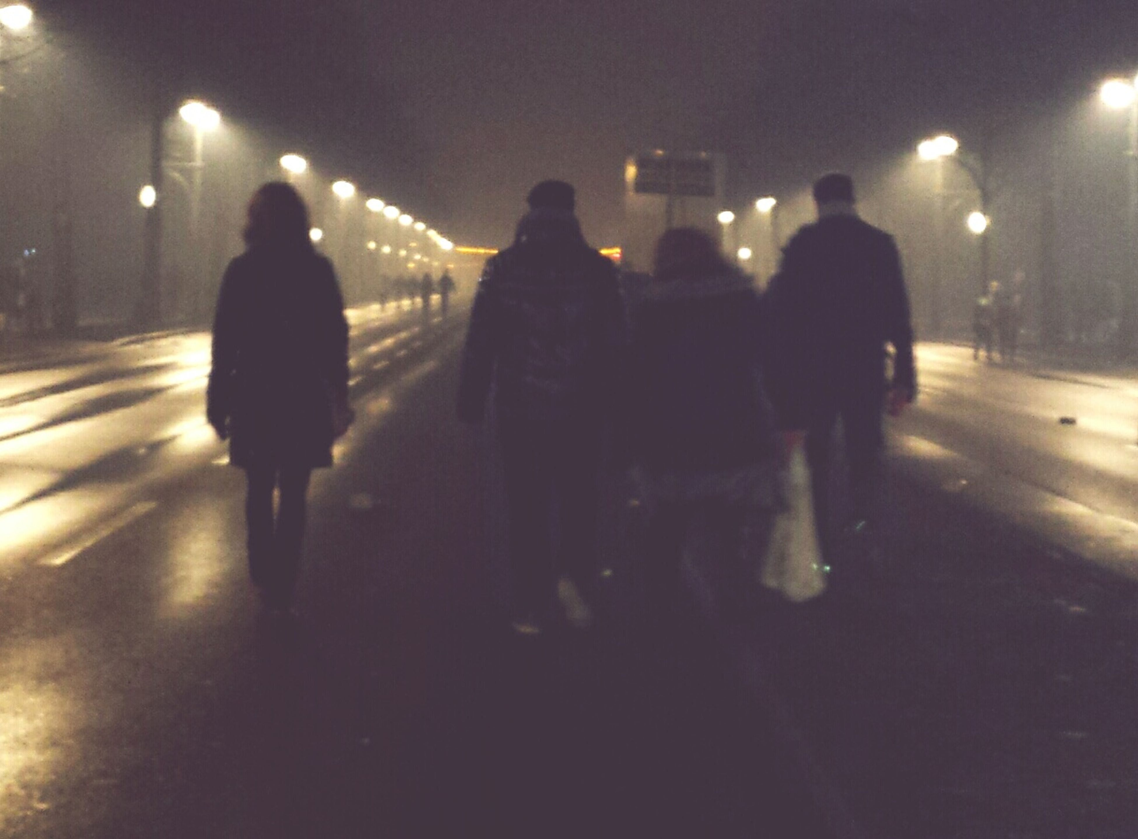night, illuminated, men, lifestyles, walking, rear view, street, full length, togetherness, person, city, leisure activity, city life, silhouette, road, standing, group of people, lighting equipment